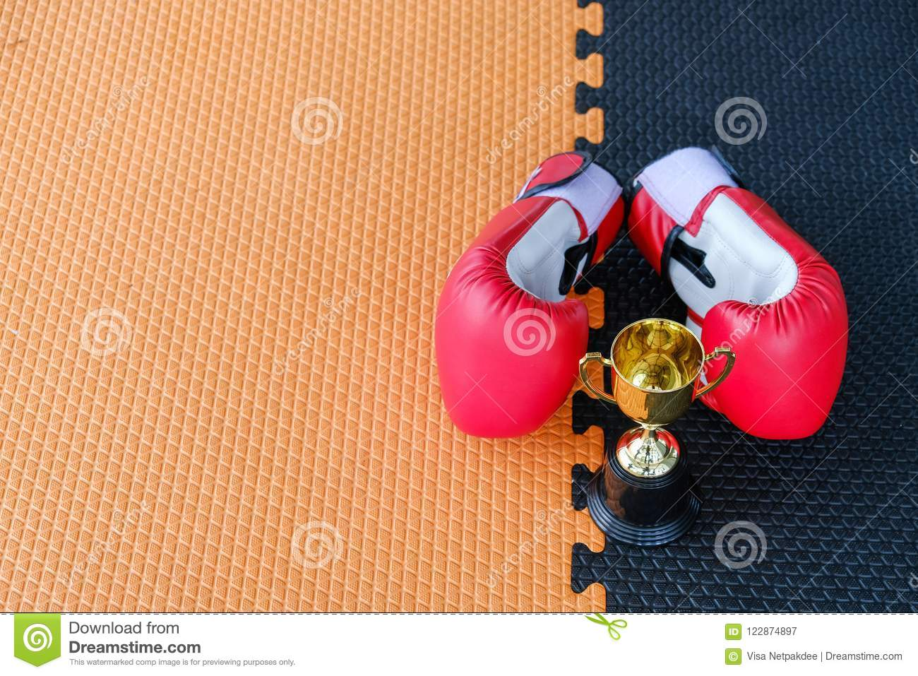Golden trophy cup with red boxing gloves