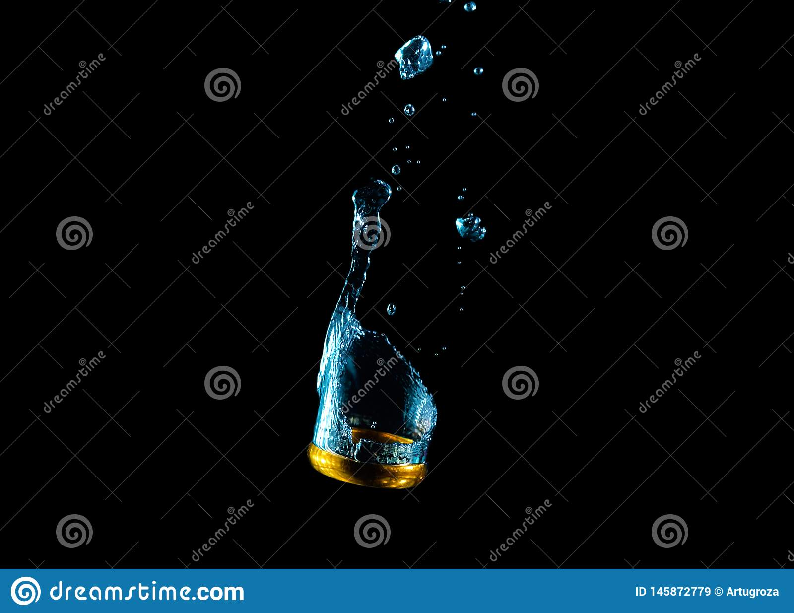 Golden wedding ring falling into the water in the bubbles. 2019 royalty free stock images