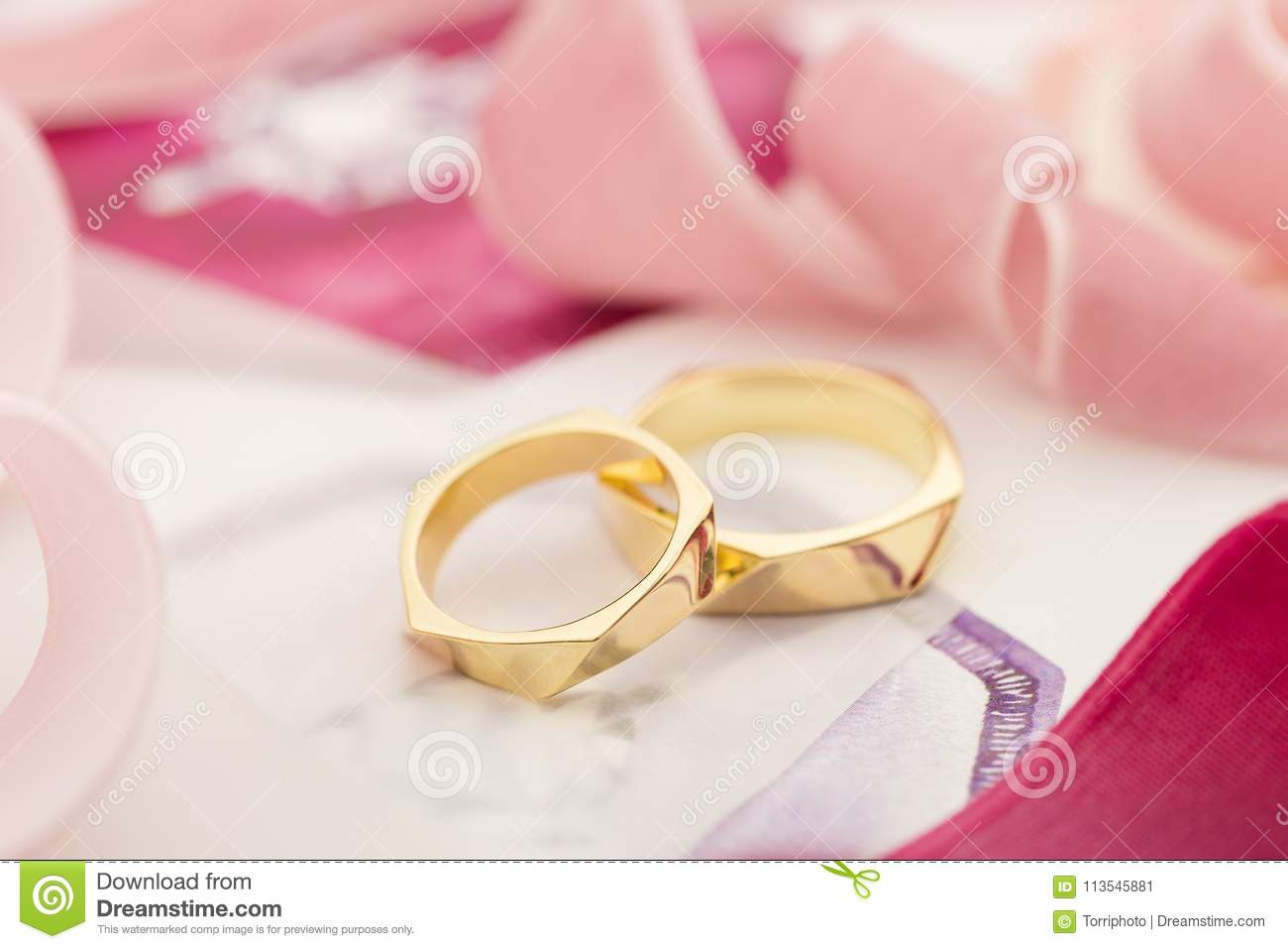 Golden Wedding Rings On Pastel Background With Pink Ribbons Stock ...