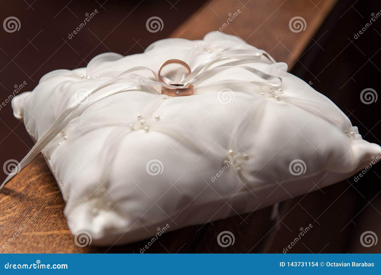 Golden wedding rings on white satin pillow on wooden hand rail