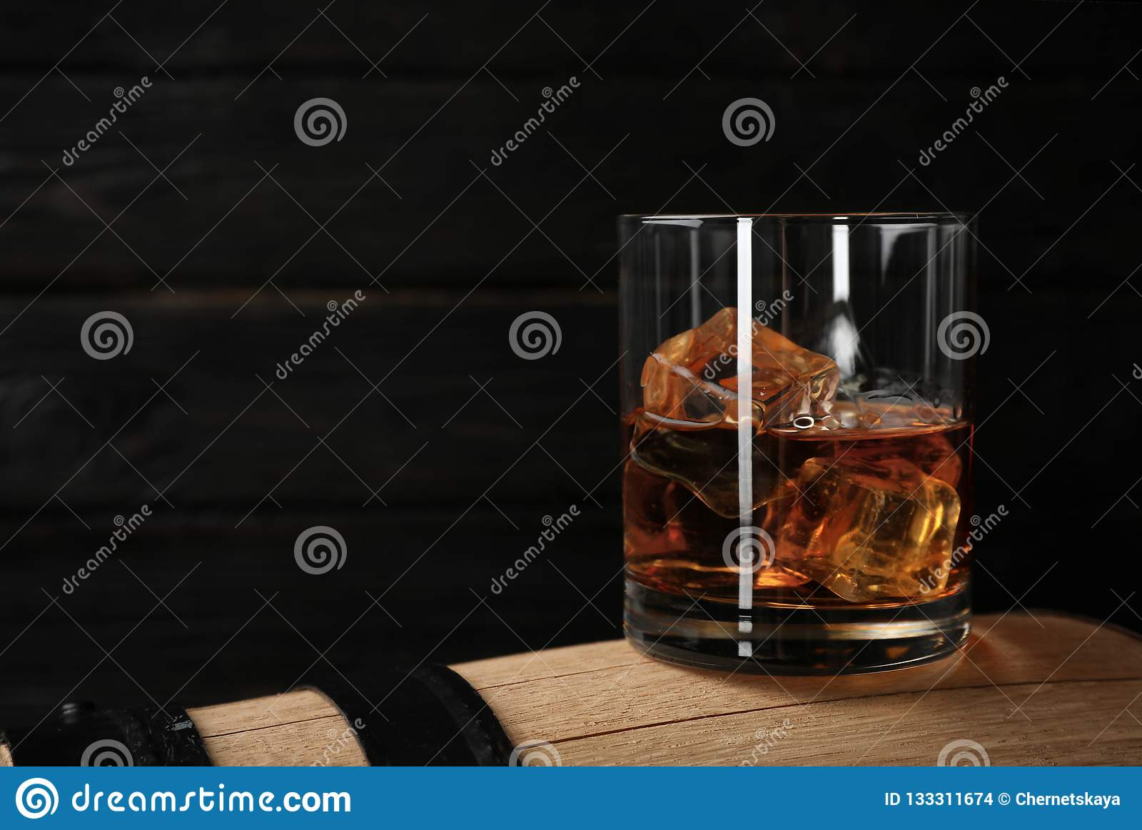Golden whiskey in glass with ice cubes on wooden barrel.
