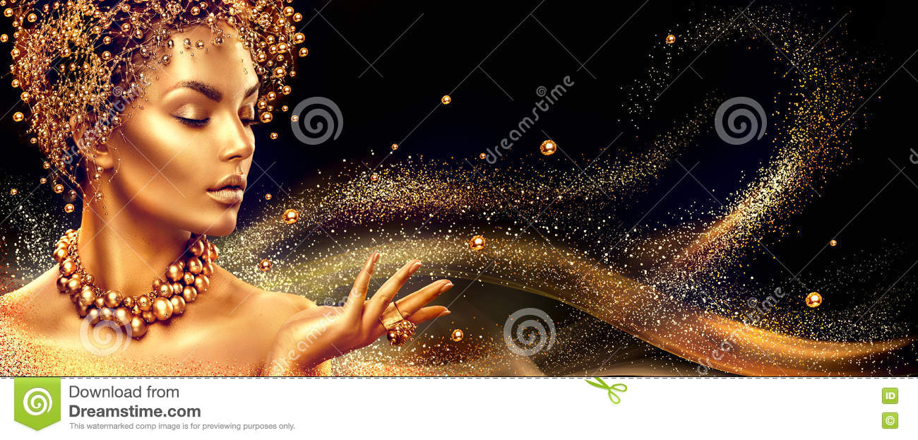 Golden woman. Beauty fashion model girl with golden make up, hair and jewellery