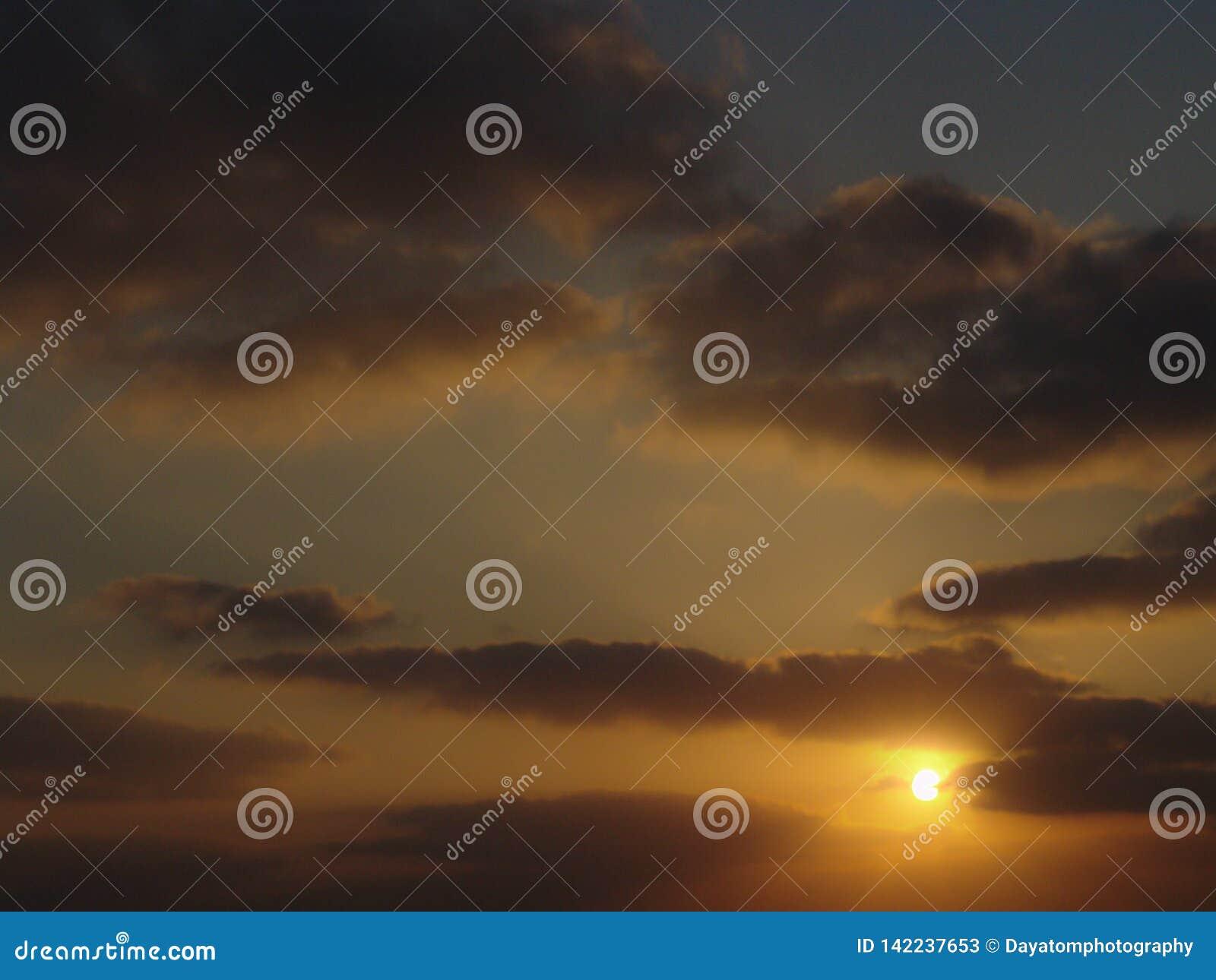 Goldene helle Sonnenuntergangansicht eines bewölkten Himmels, Sonne, die nahe gelb-orangeen dunklen Wolken sich versteckt