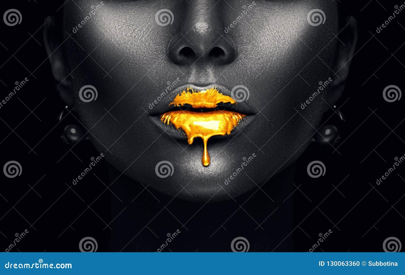 Goldfarbentropfenfänger von den sexy Lippen, goldene flüssige Tropfen auf schönem vorbildlichem Mädchenmund, dunkles schwarzes Ha