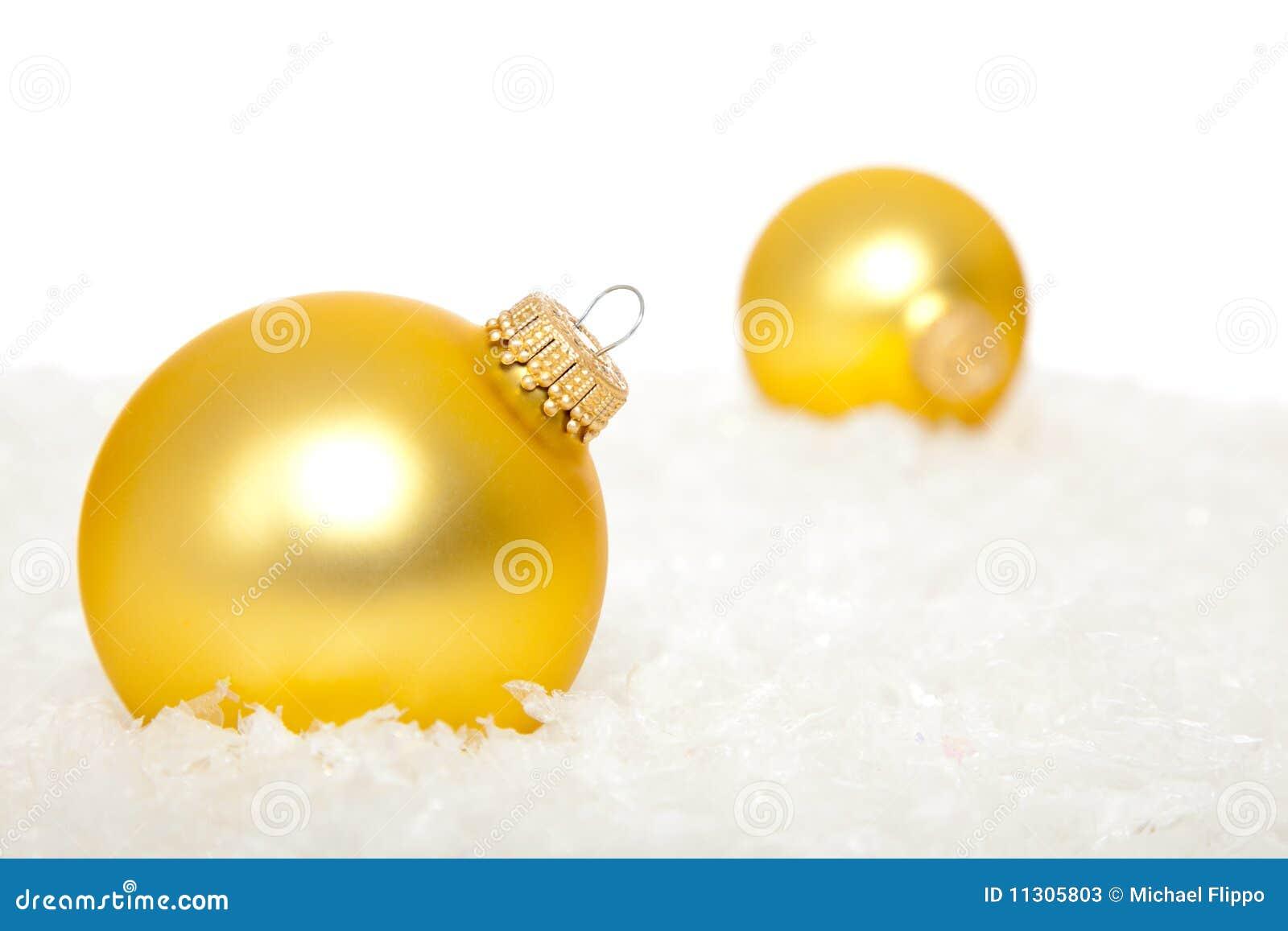 Goldweihnachtsverzierungen im Schnee