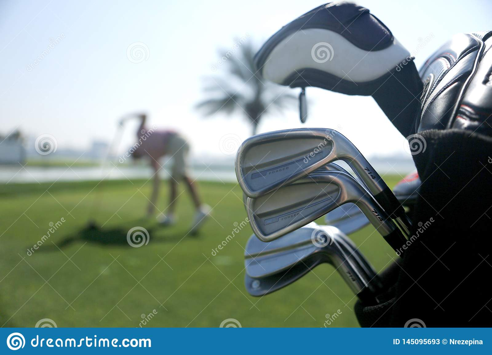 Golf bag with clubs on the plan and with the player before swing in the background