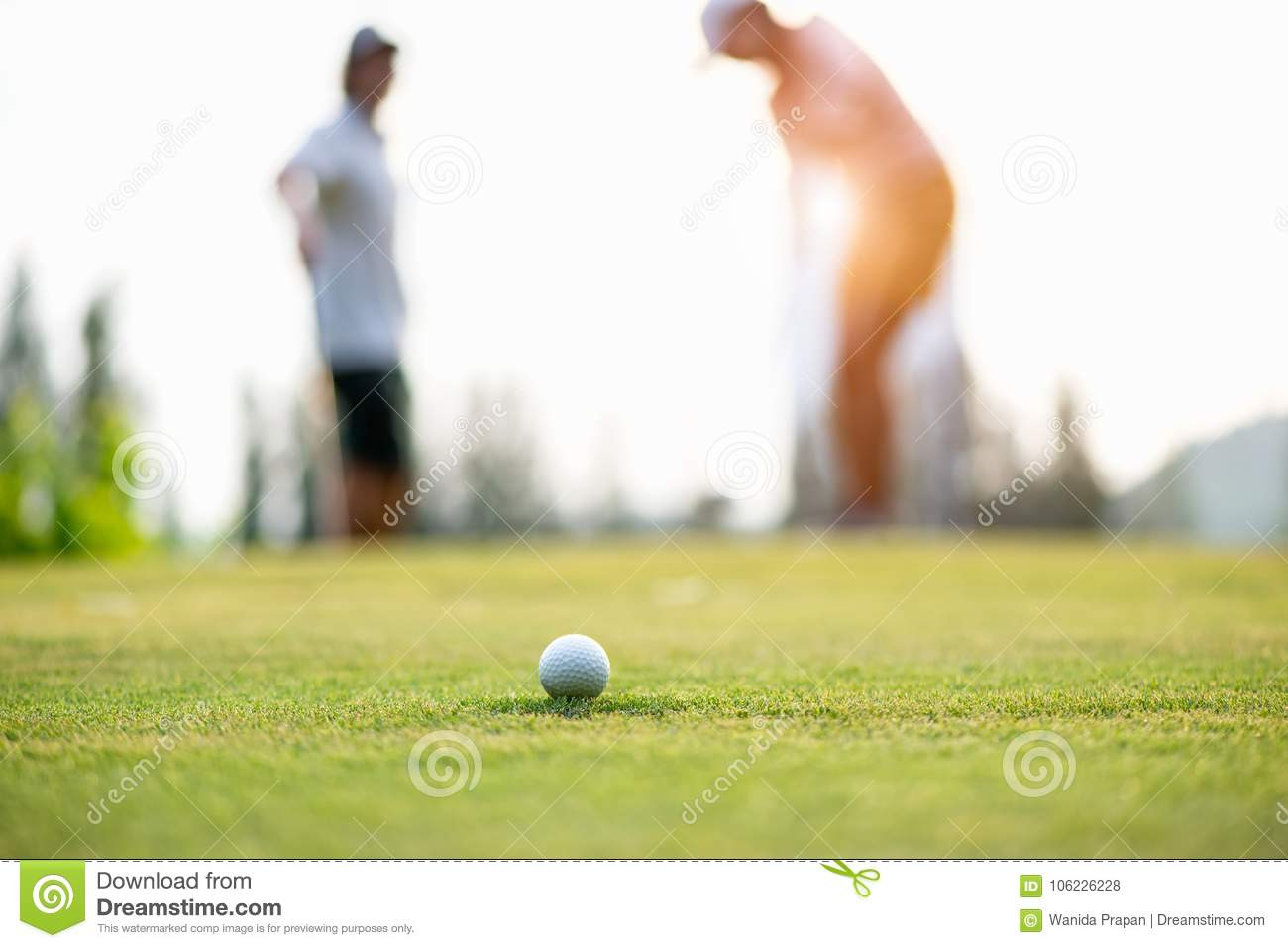 Golf ball approach to the hold on the green. Couple golf player putting golf ball in the background.