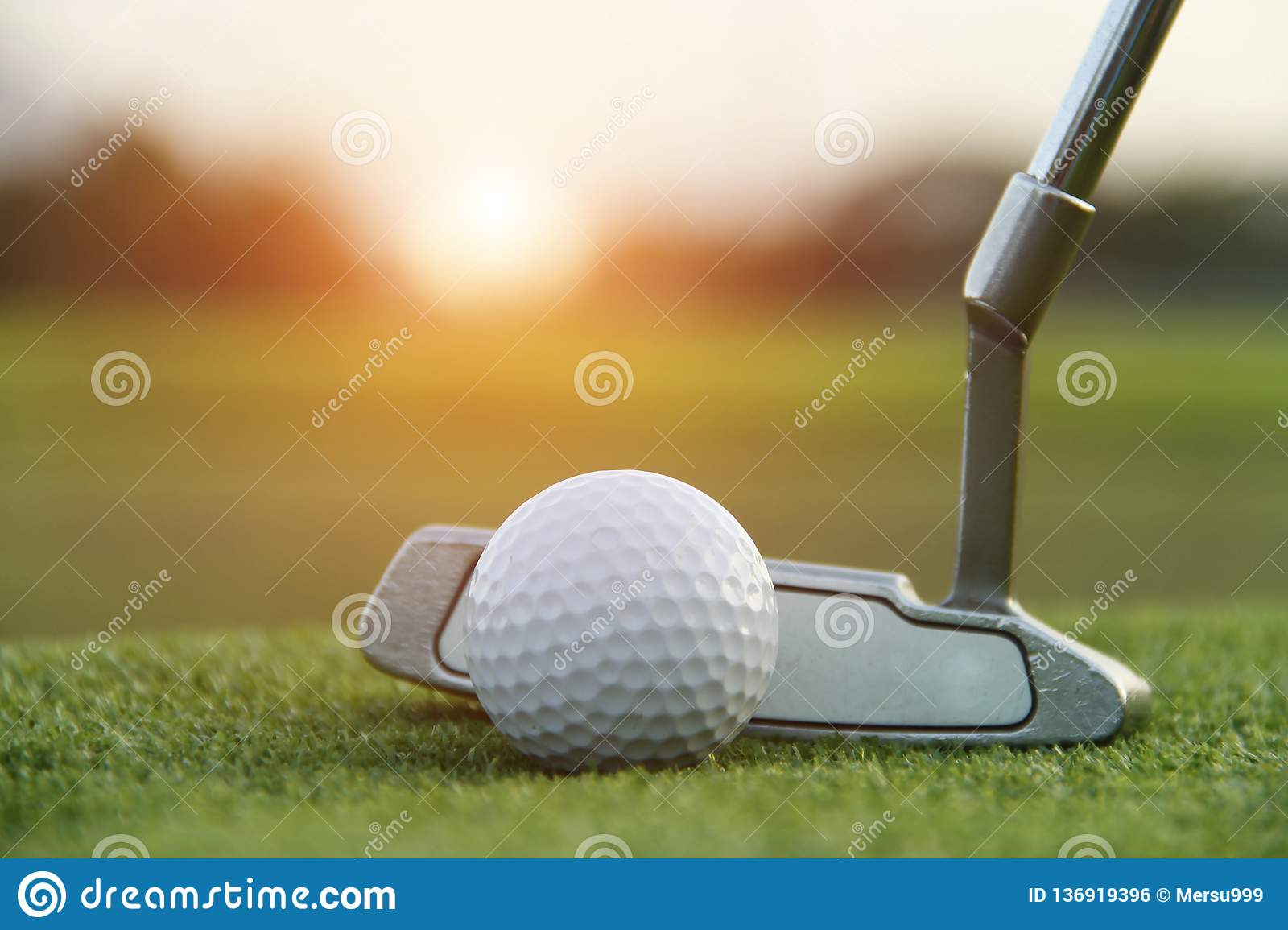 Golf ball and golf club in beautiful golf course at sunset background