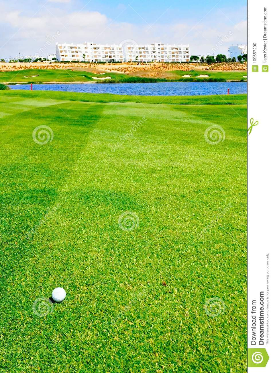 Golf ball on fairway with water hazard in front of green