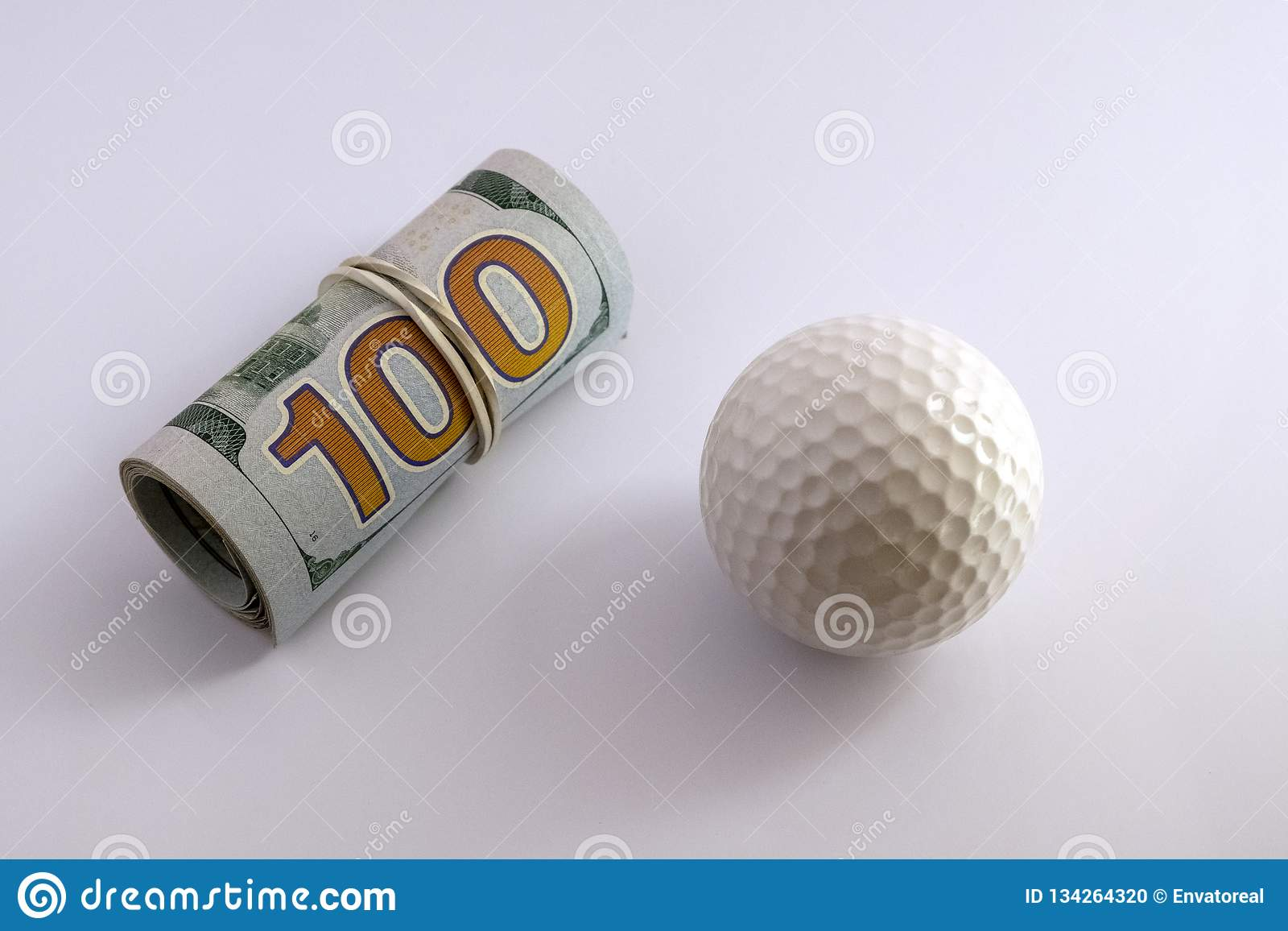 Golf ball next to a roll of hundred dollar bills of the USA with a white rubber band. The concept of sports betting, golfing