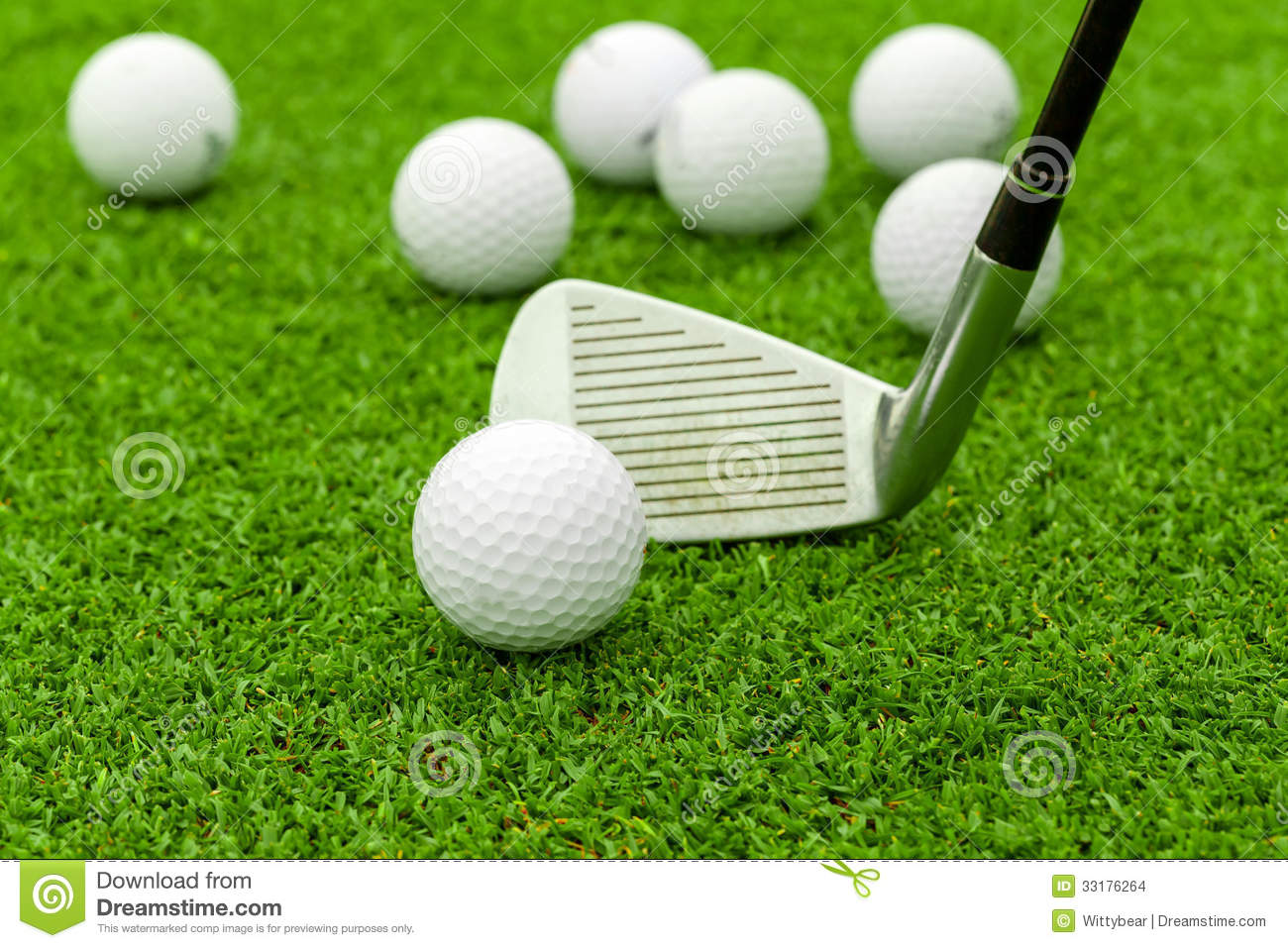 Golf ball on tee in front of driver on green course