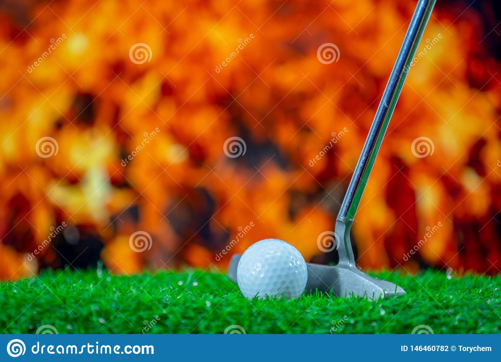 Golf club and golf ball on grass
