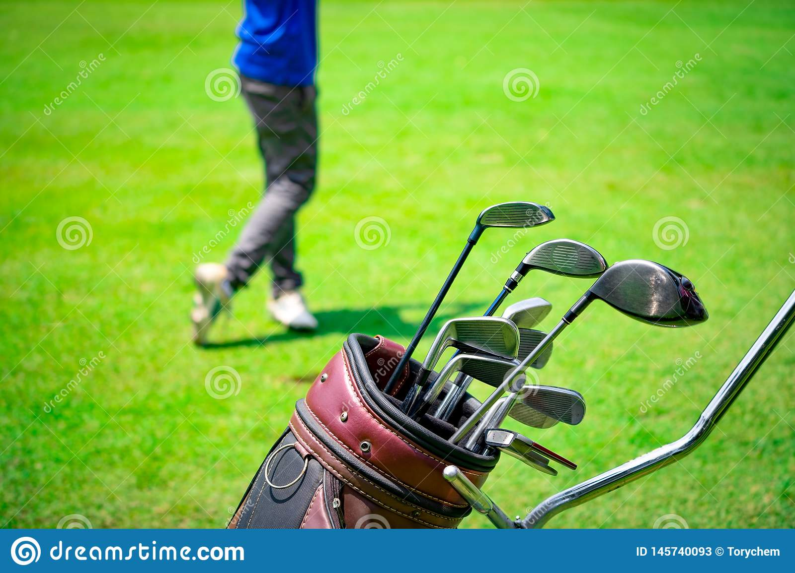 Golf club suit in bag cart and blurred golfer hitting golf ball