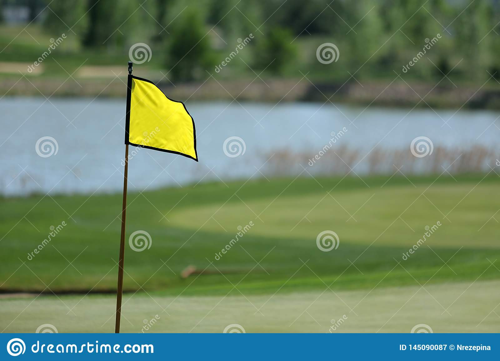 A golf course with roads, bunkers and ponds and with flag
