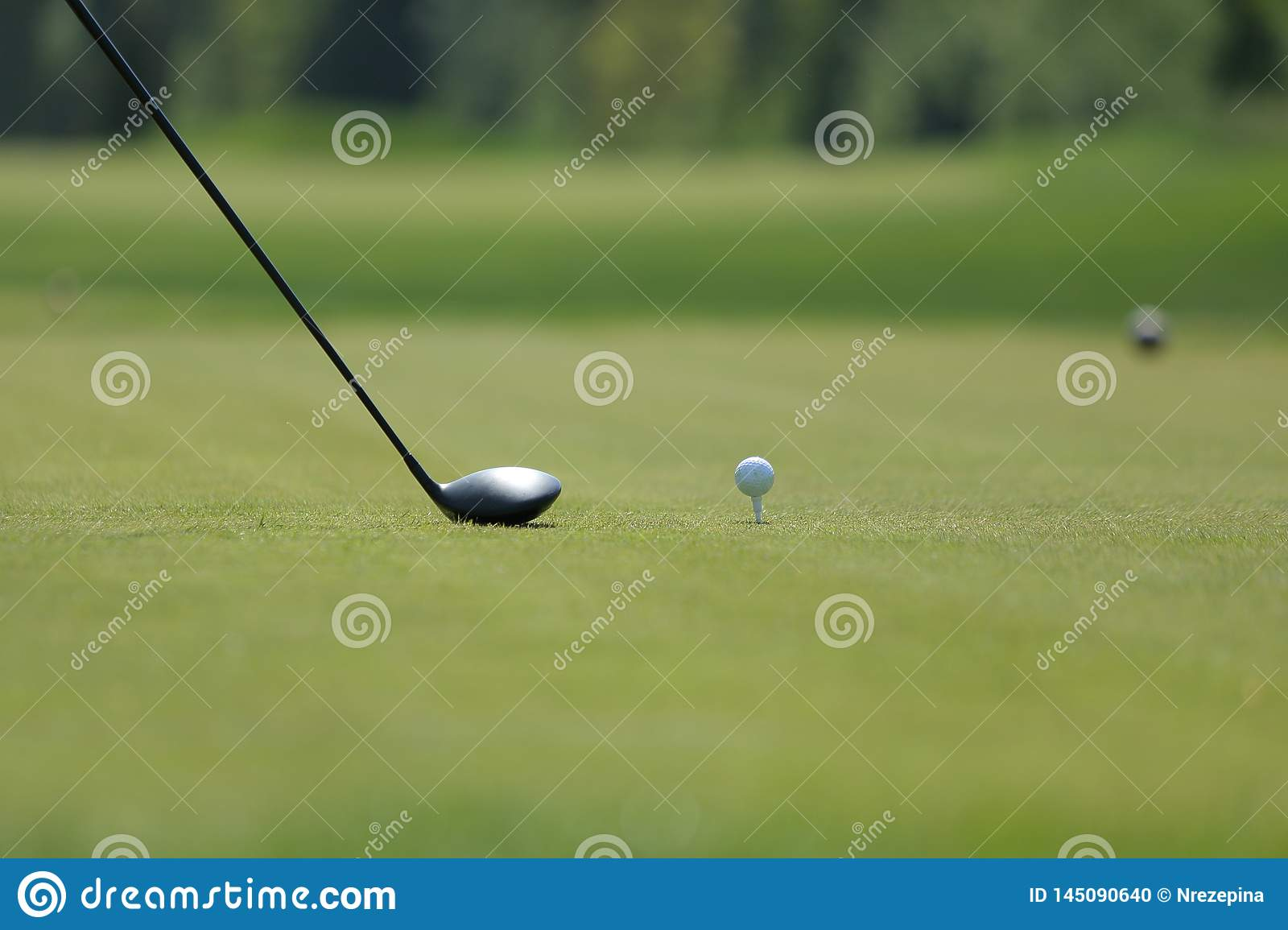 A golf driver with ball on a tee on the golf course