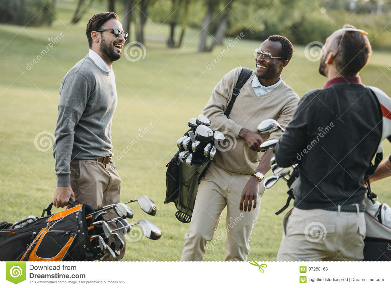 Golf players with golf clubs having fun on golf course