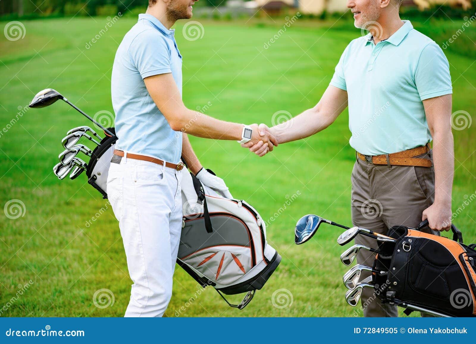Golfare skakar händer med de