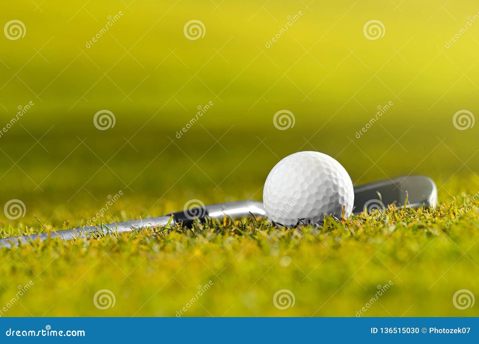 Golfbal en club op gras