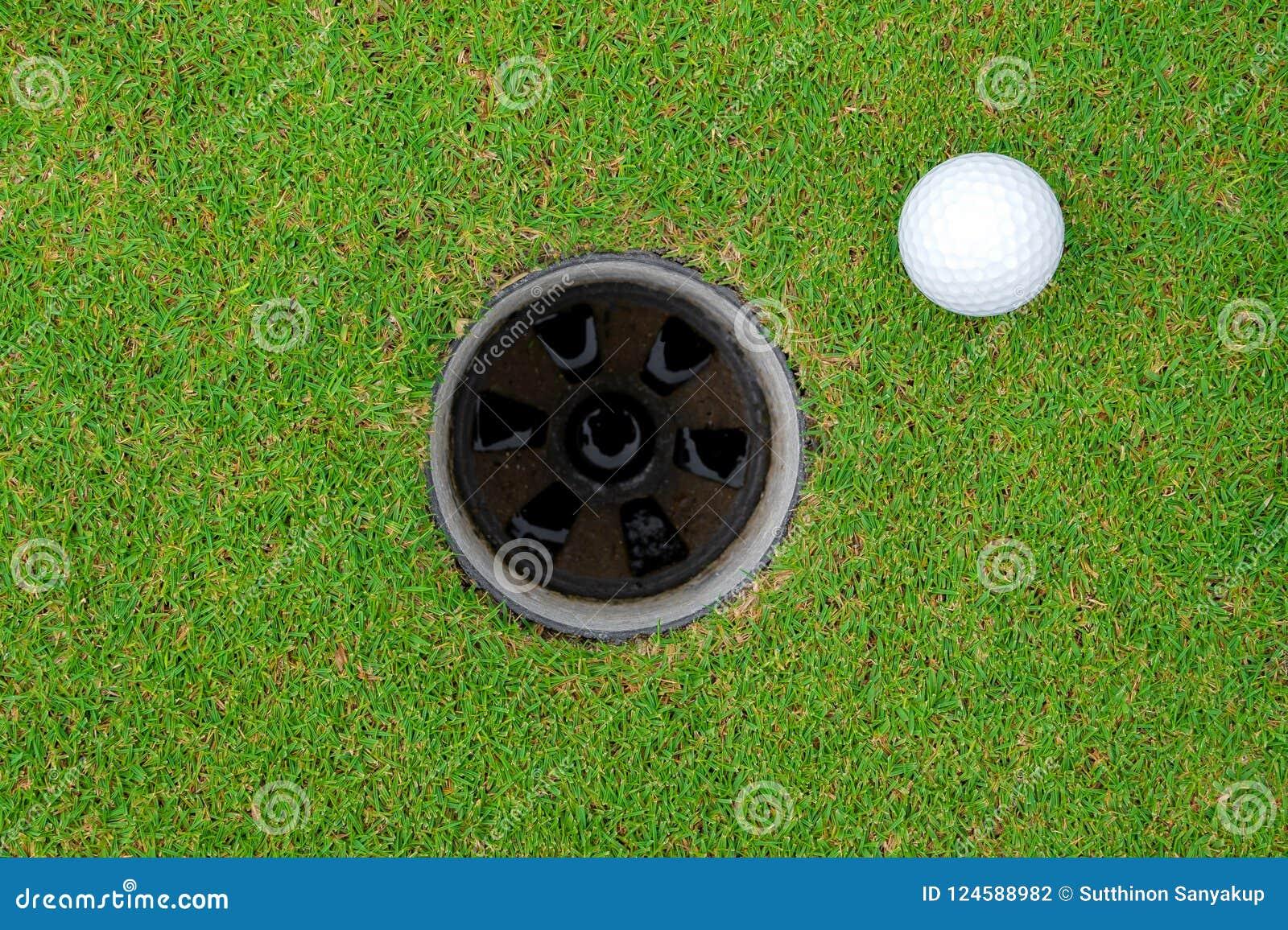 Golfbal en golfgat op groen gras