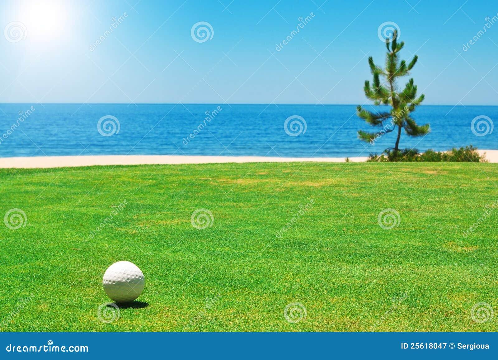Golfbal op groen gras met de oceaan.