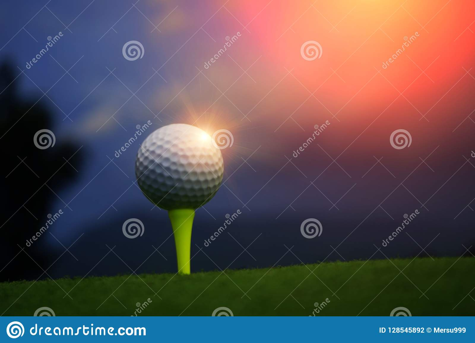 Golfboll på utslagsplats i härlig golfbana på solnedgångbakgrund