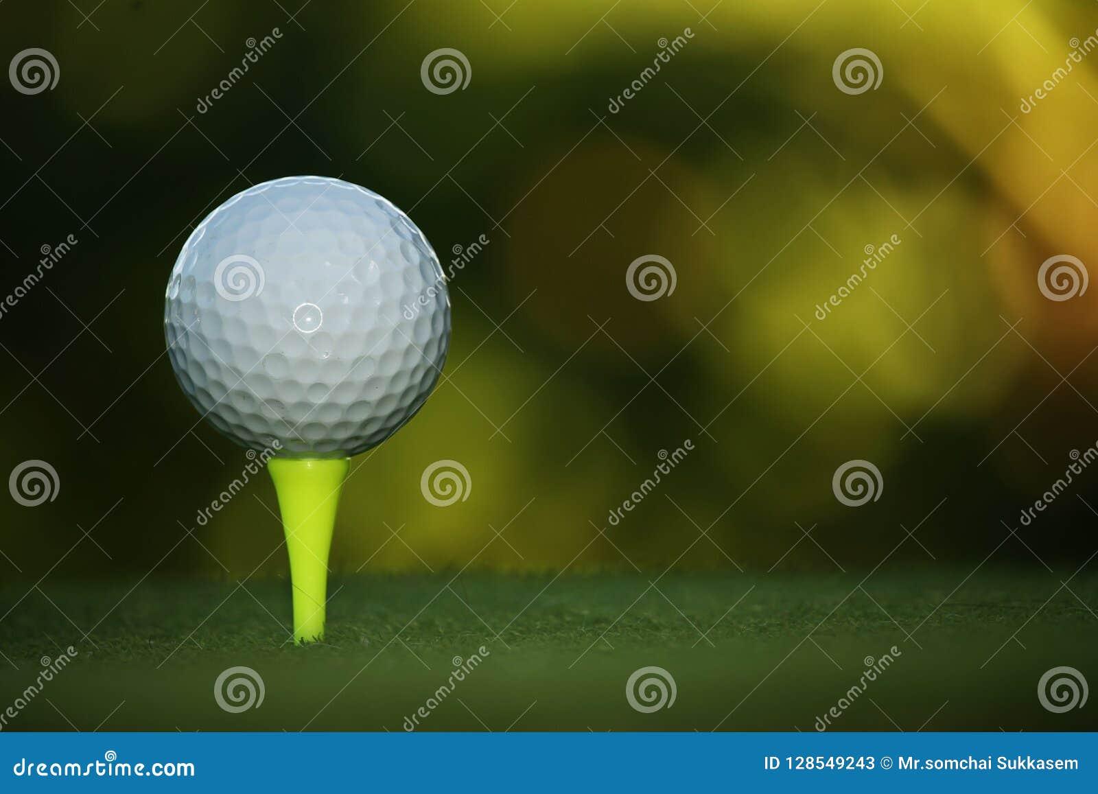 Golfboll på utslagsplats i härlig golfbana på solnedgången