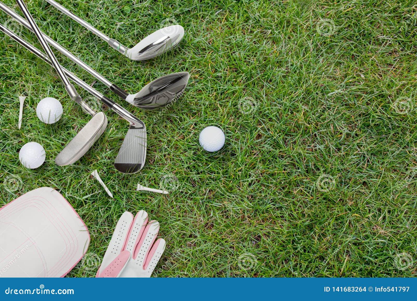 Golfclubs, Golfbälle, Golfhandschuh und Kappe auf Gras