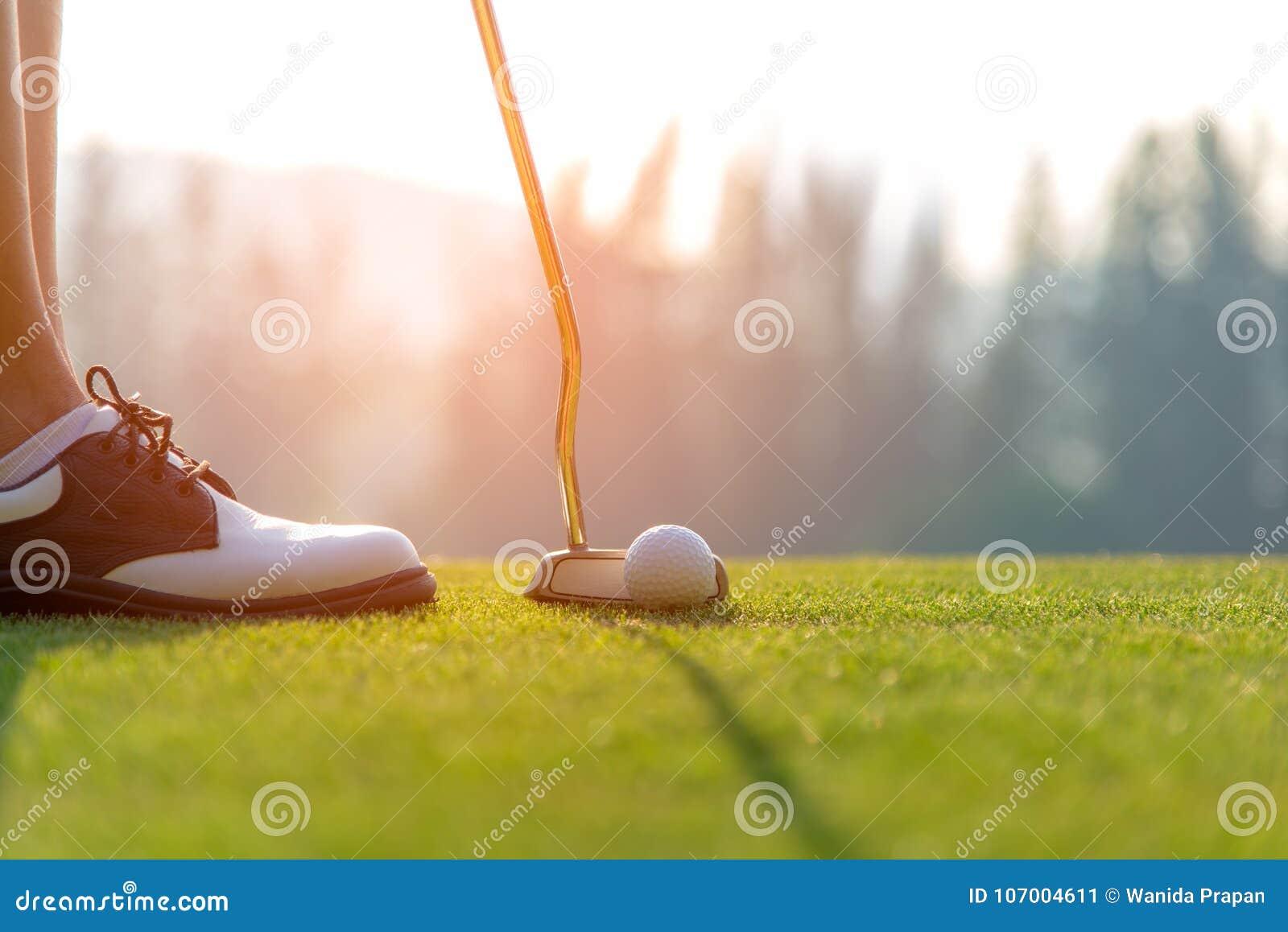 Golfer asian woman putting golf ball on the green golf on sun set evening time.
