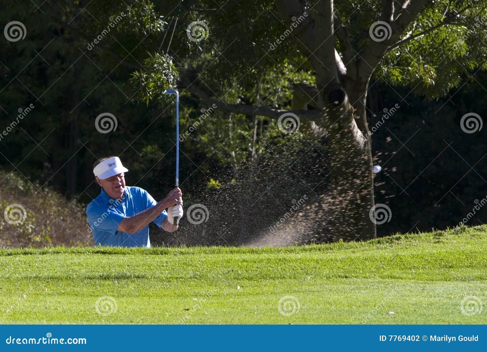 Golfer hitting from bunker