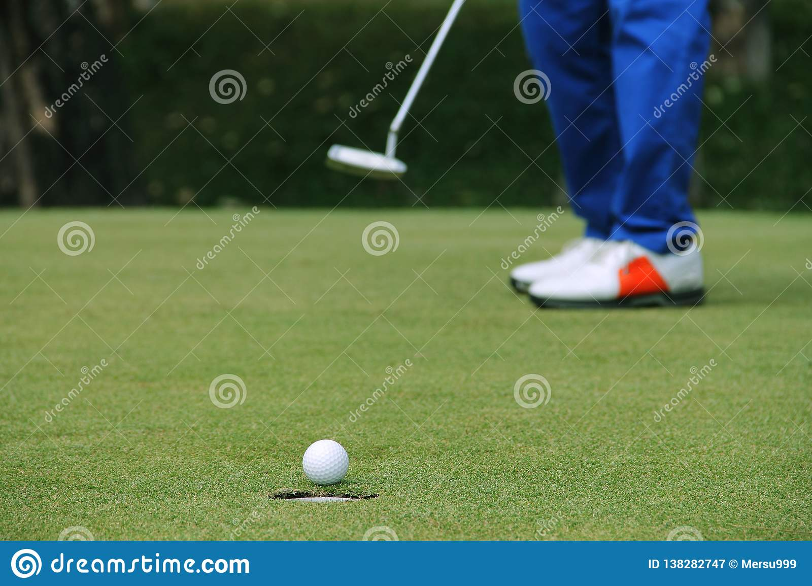 Golfer putting golf ball on the green golf