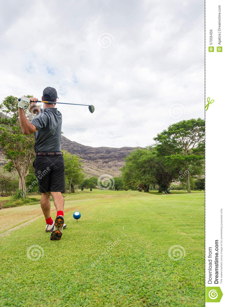 Golfer tees off from tee box to fairway