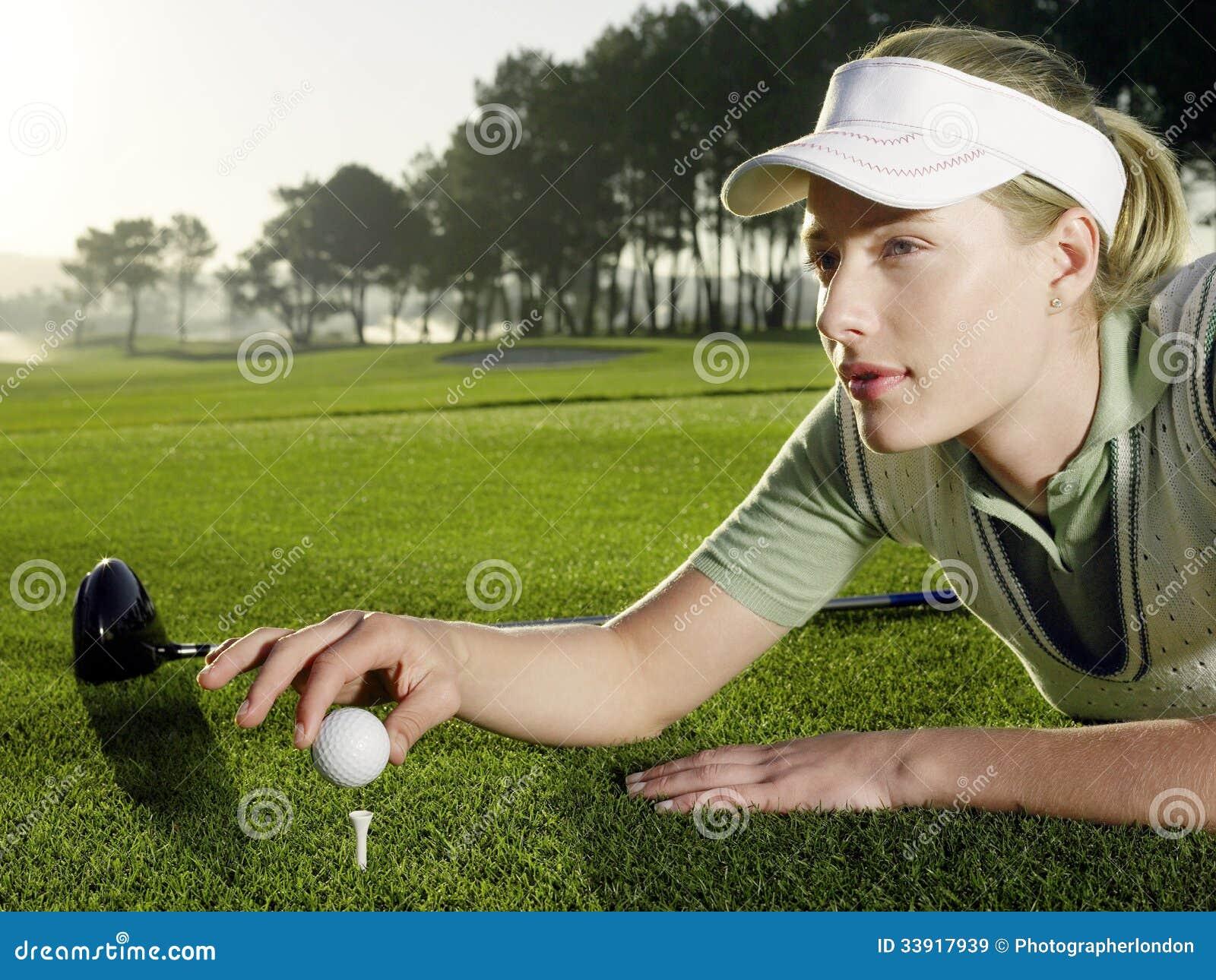 Golfeur féminin plaçant la boule sur la pièce en t