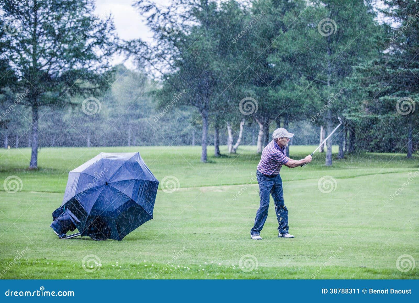 Golfeur un jour pluvieux Swigning dans le fairway