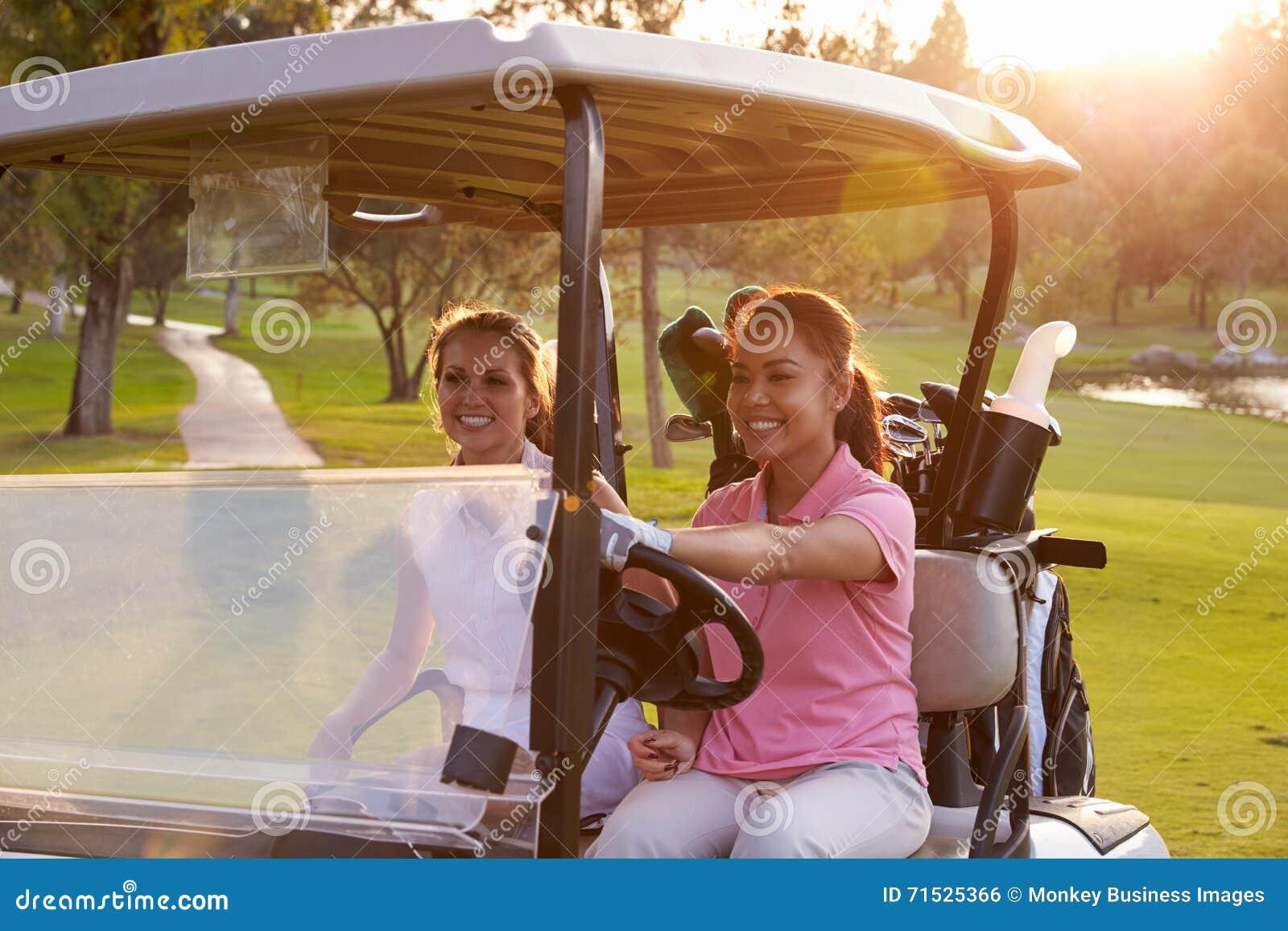 Golfeurs féminins conduisant le boguet le long du fairway du terrain de golf