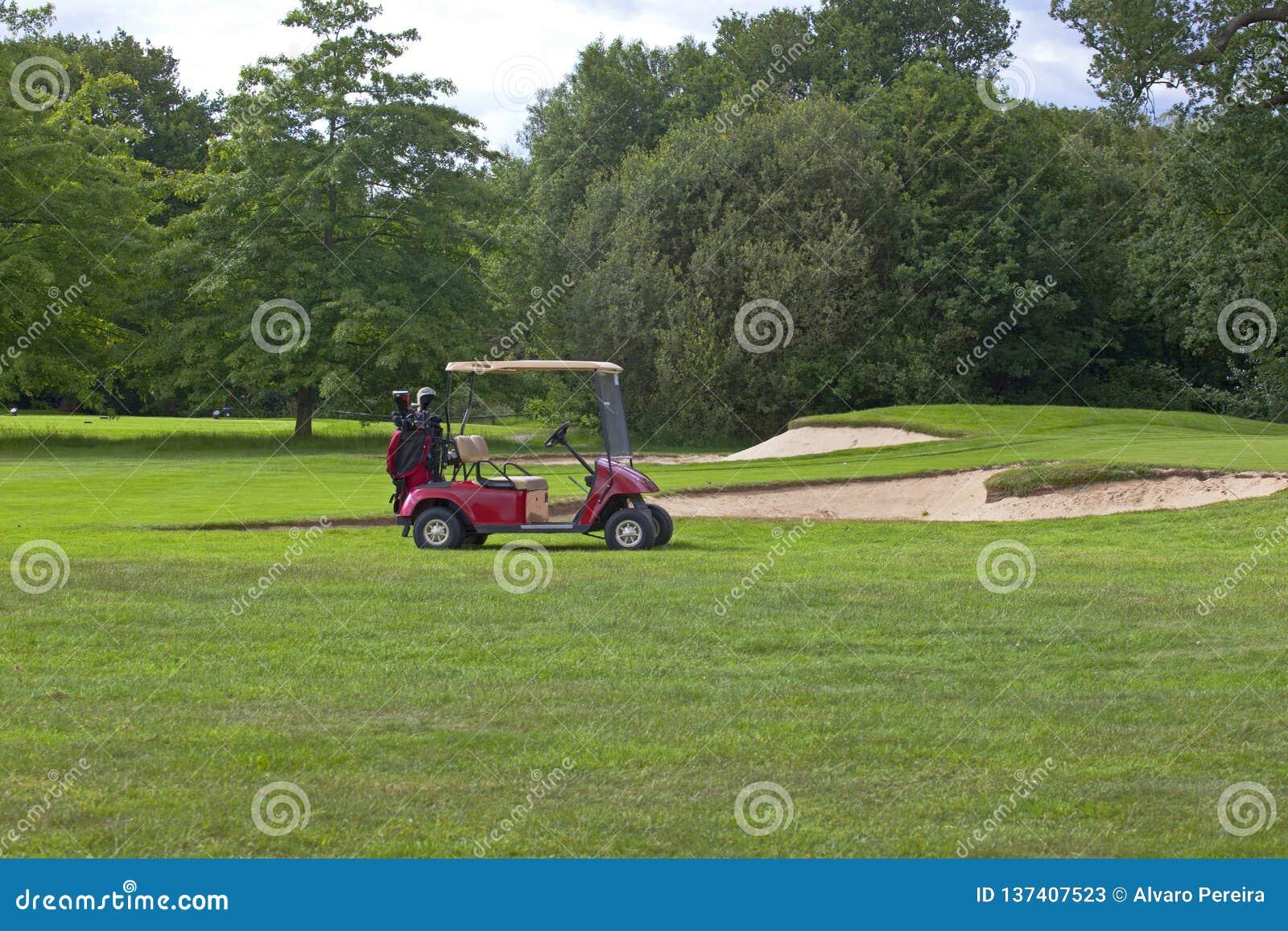 Golfgräsplan med den röda golfvagnen