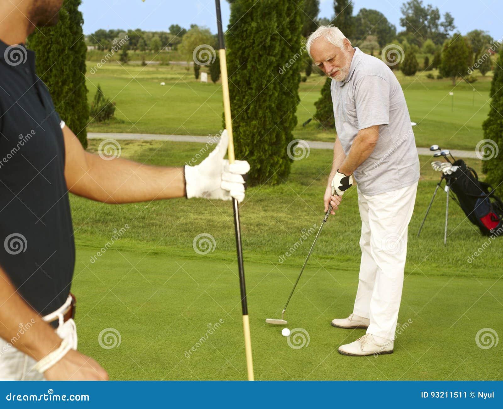 Golfista mayor que concentra en bola