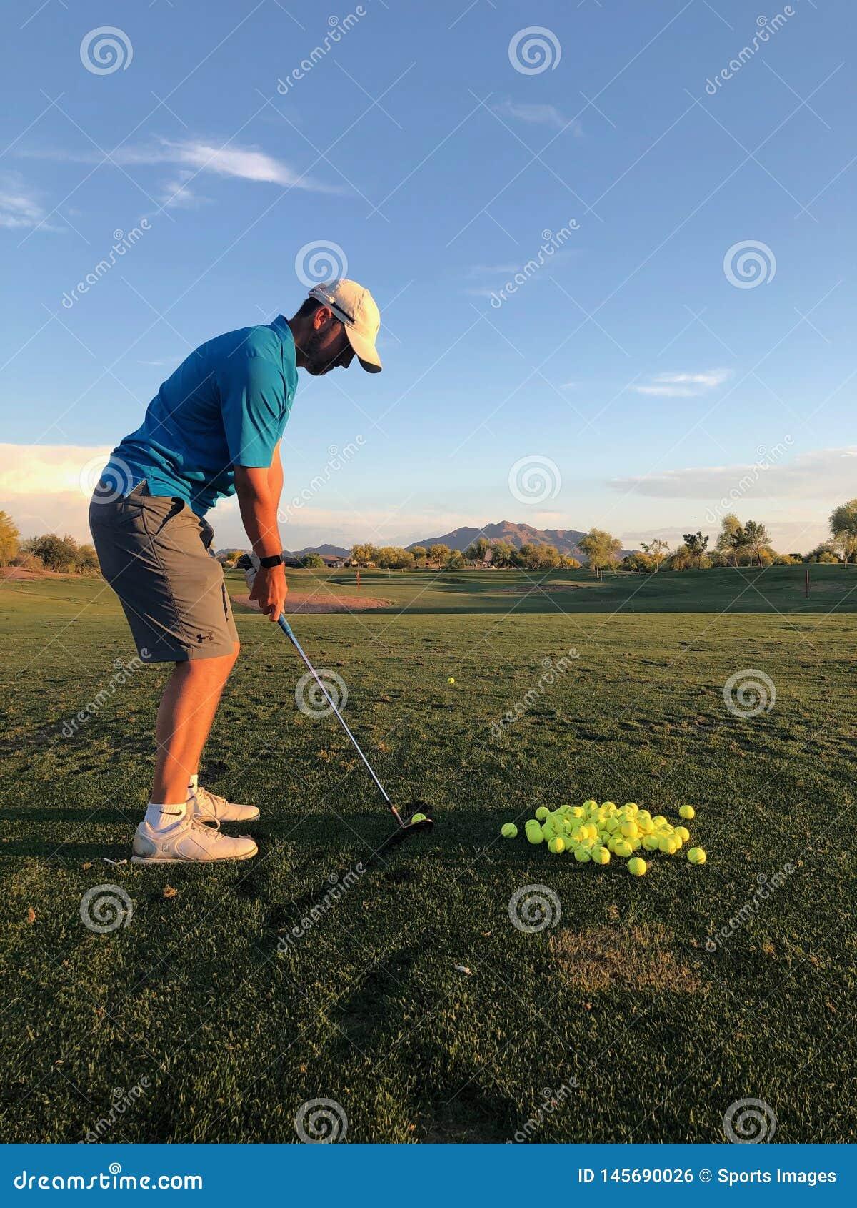 Golfista que golpea las pelotas de golf para la práctica de una visión trasera