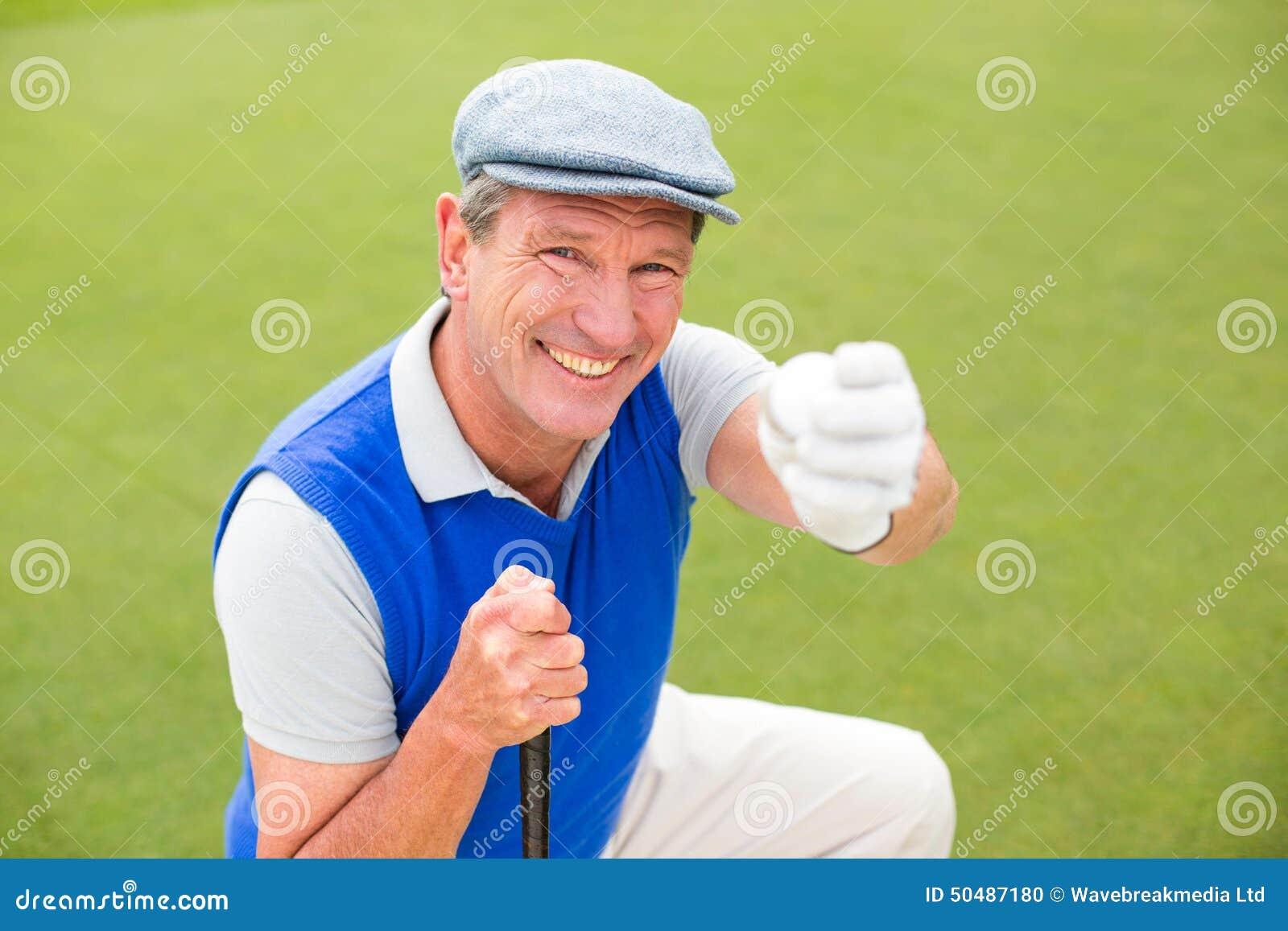 Golfista sonriente que se arrodilla en el putting green
