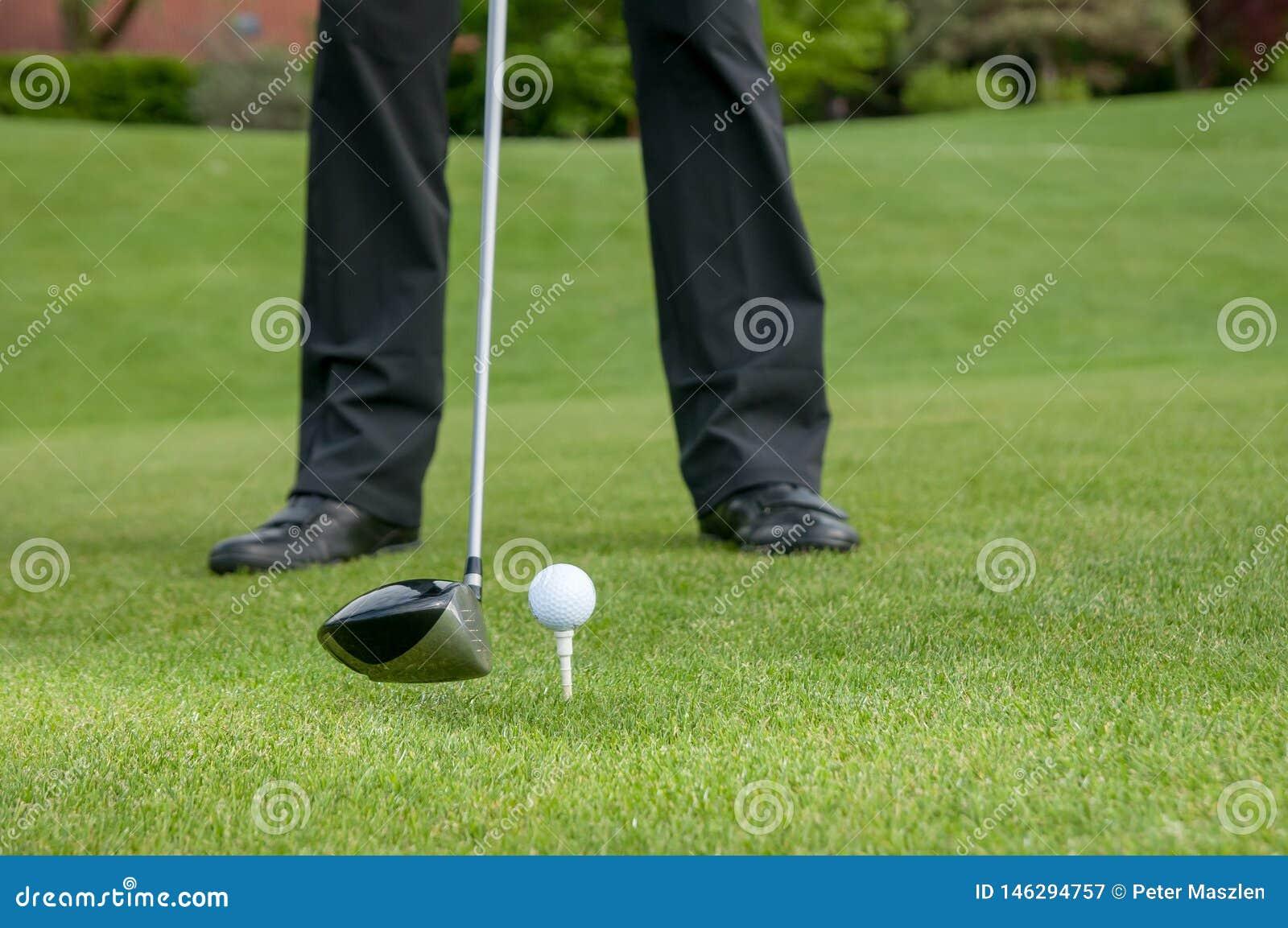 Golfista teeing daleko na polu golfowym