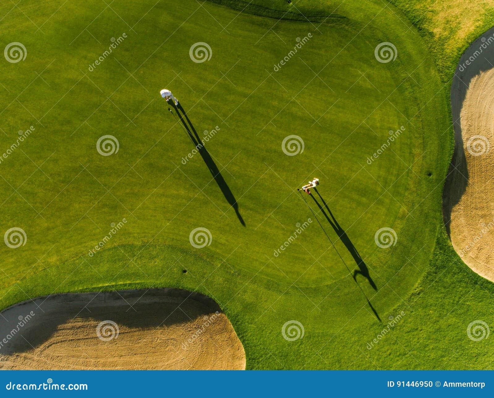 Golfistas profesionales que juegan en putting green