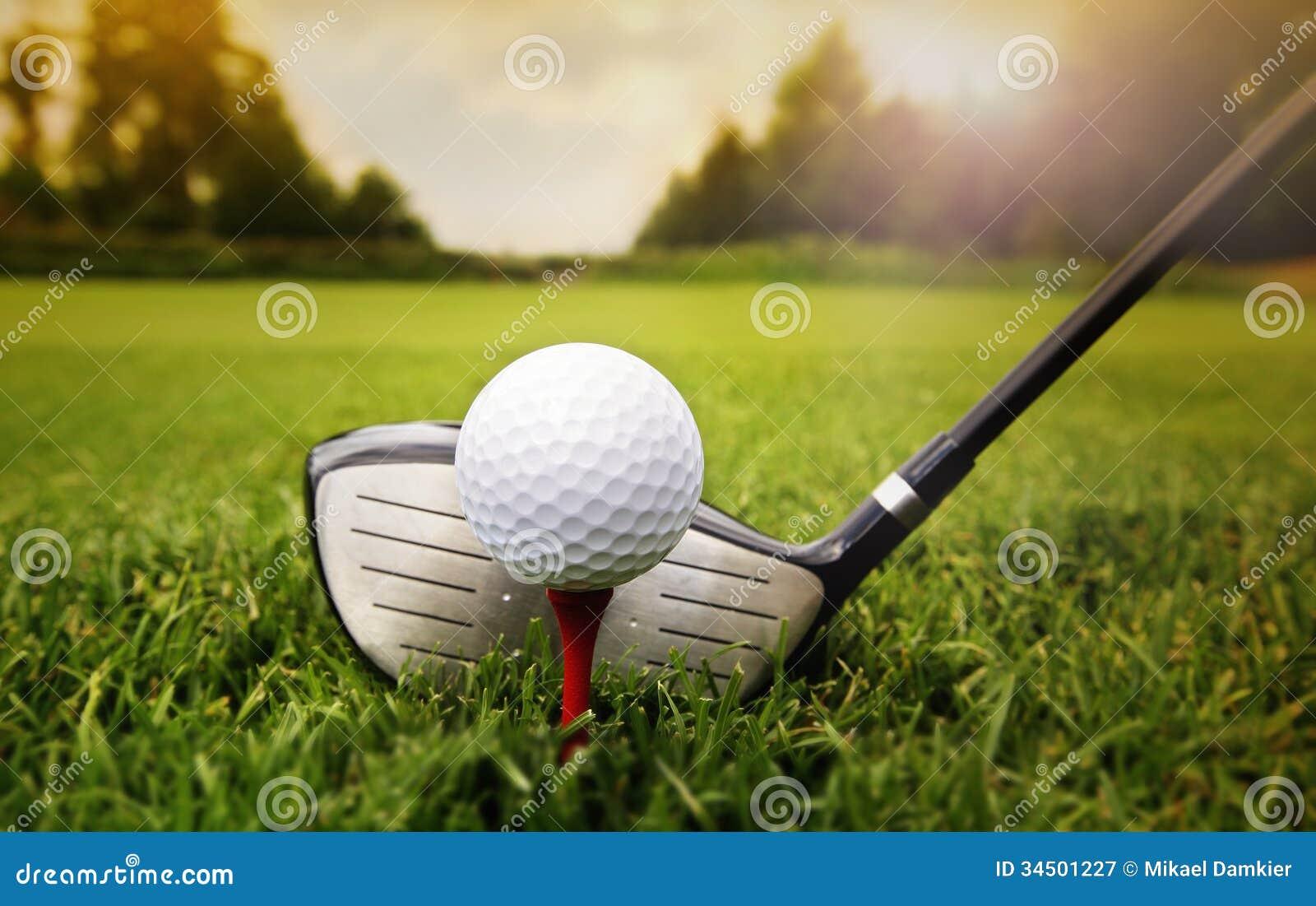 Golfklubb och boll i gräs