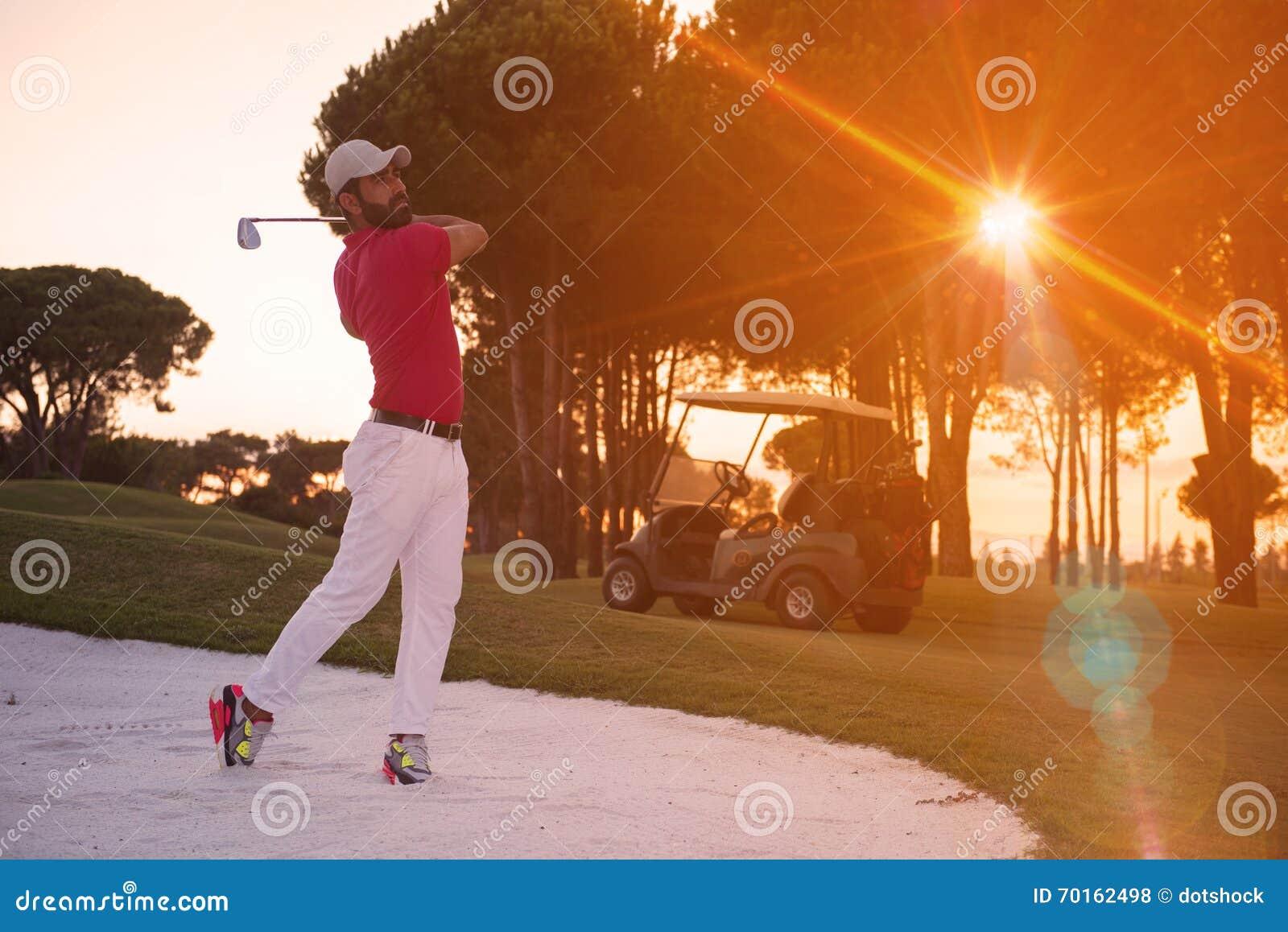 Golfspeler die die een zandbunker raken op zonsondergang wordt geschoten