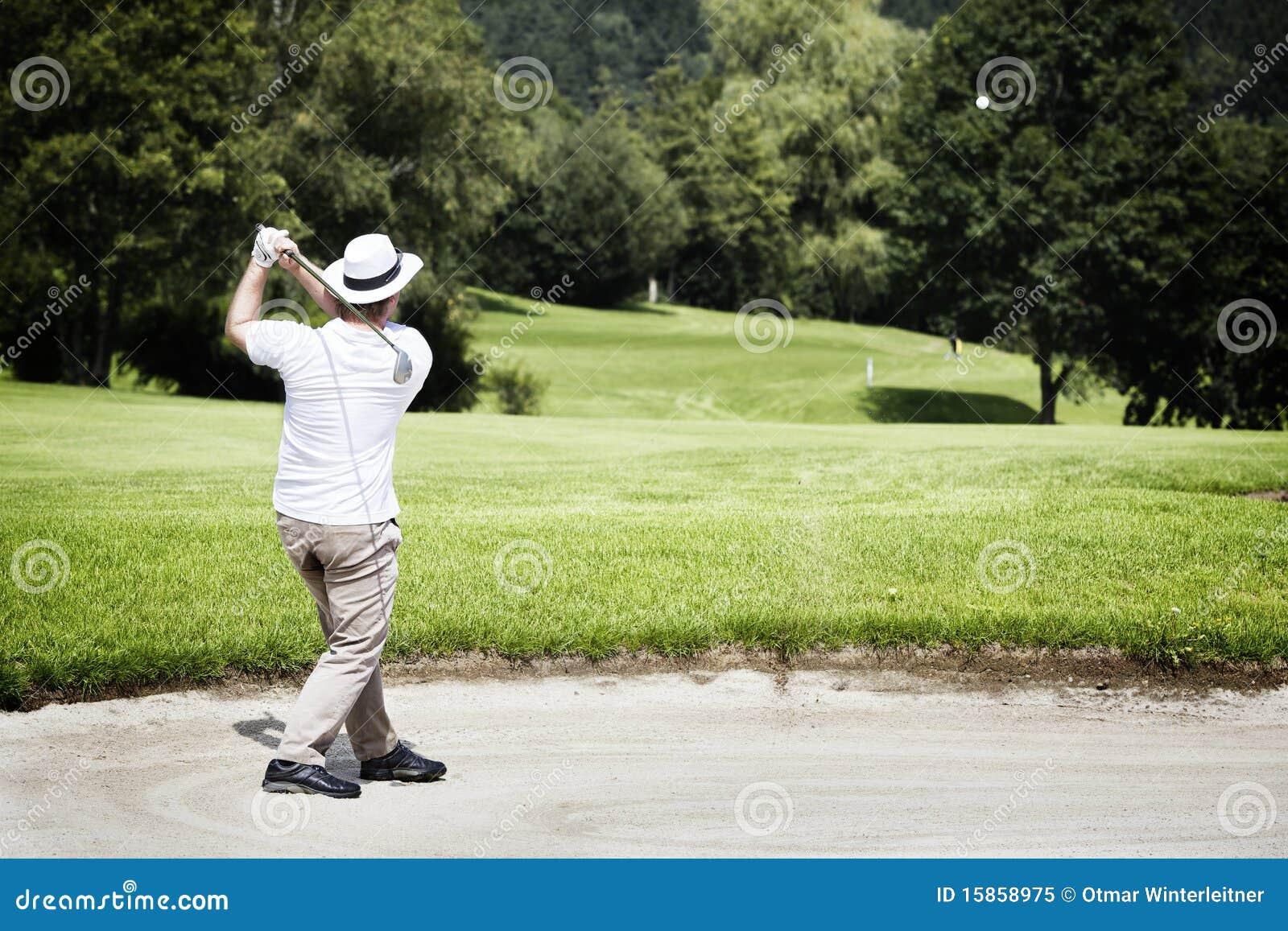 Golfspieler, der im Bunker abbricht.
