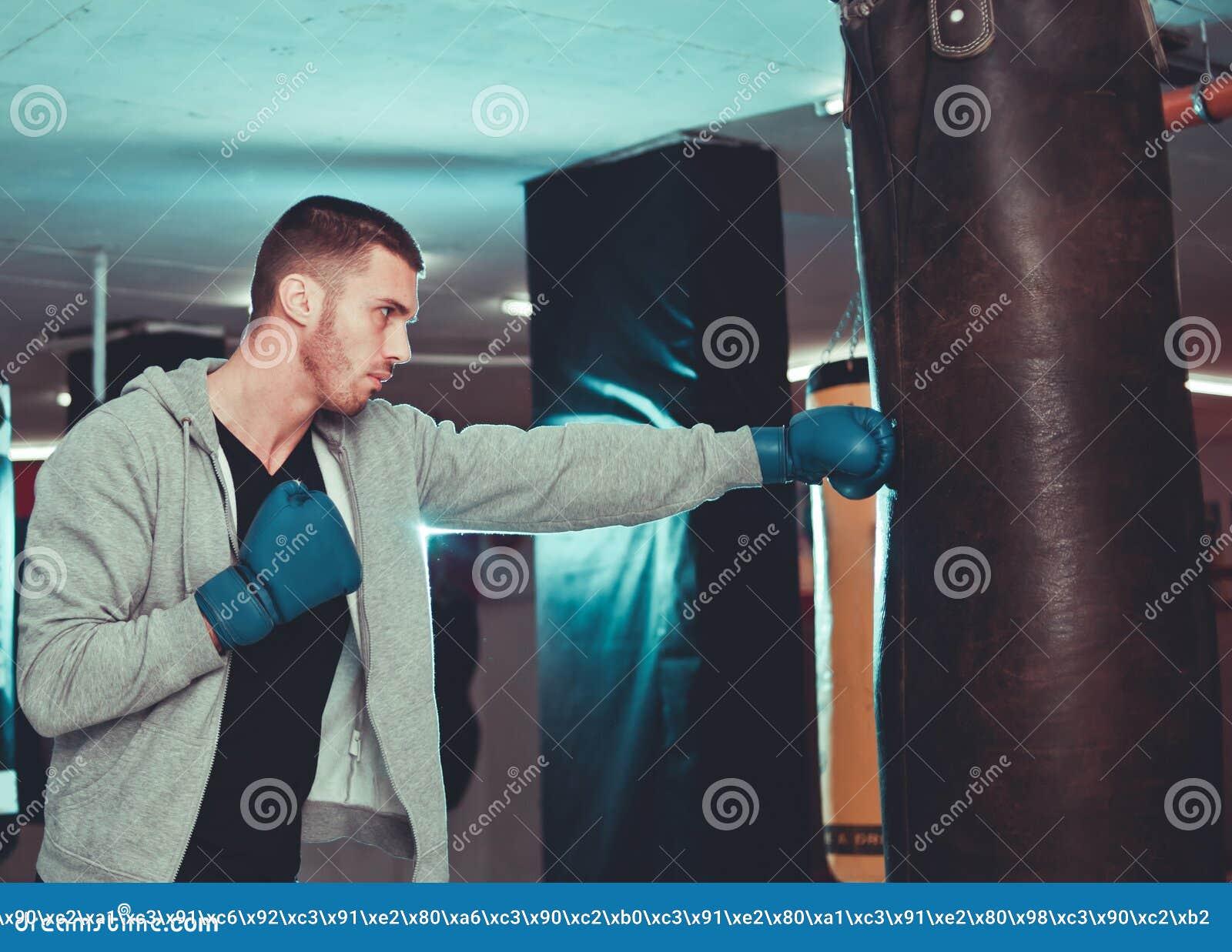 Golpe directo concentrado del boxeador con el saco de arena