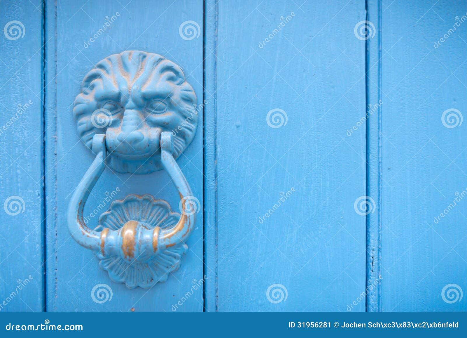 Golpeador de puerta principal del león en una puerta de madera vieja