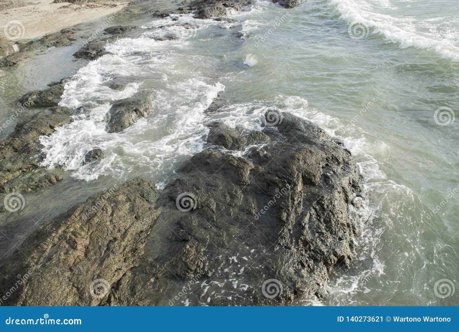 Golven die op rotsen verpletteren