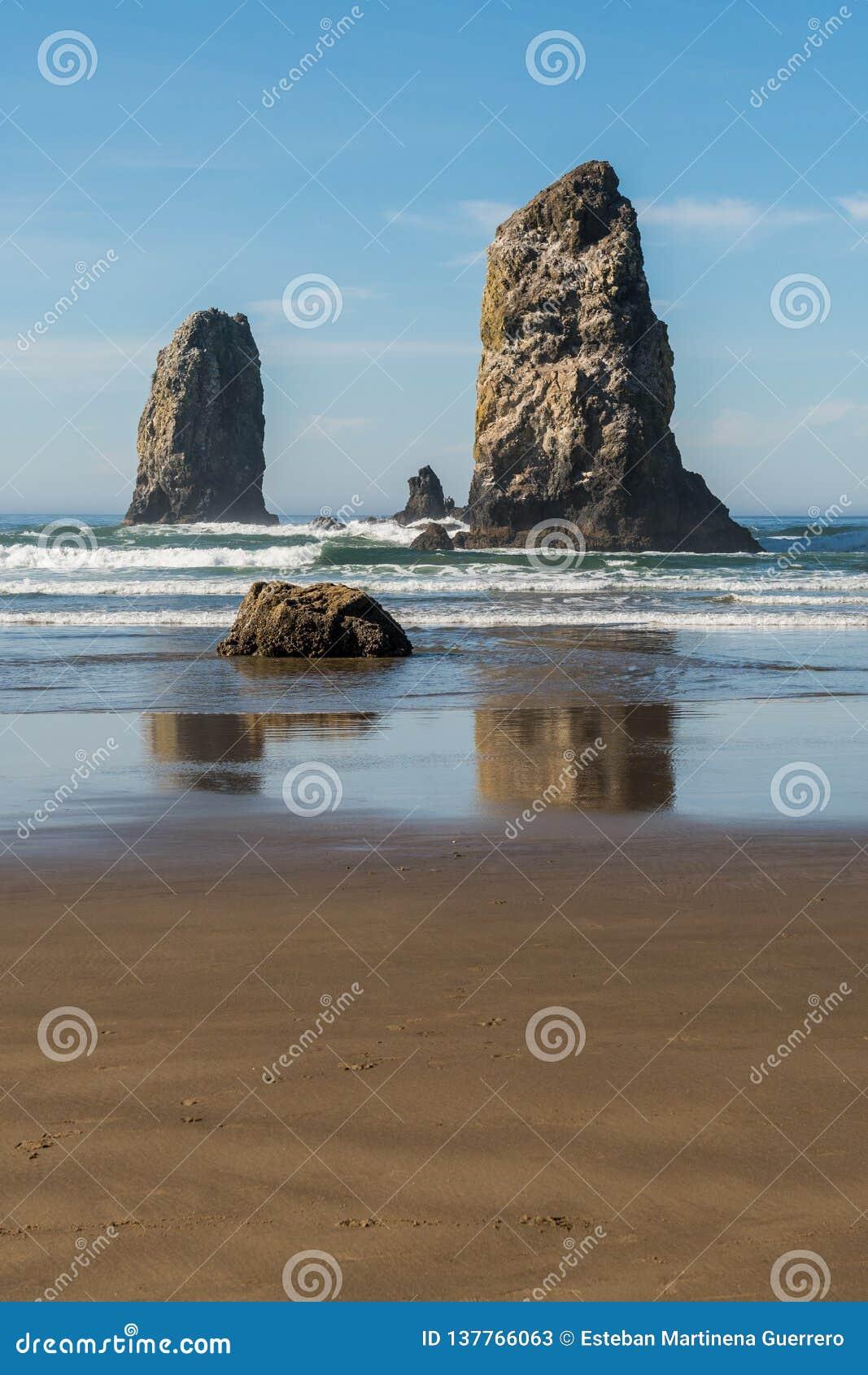 Golven die op verticale rotsen verpletteren die in Kanonstrand uitpuilen, Oregon, de V.S.