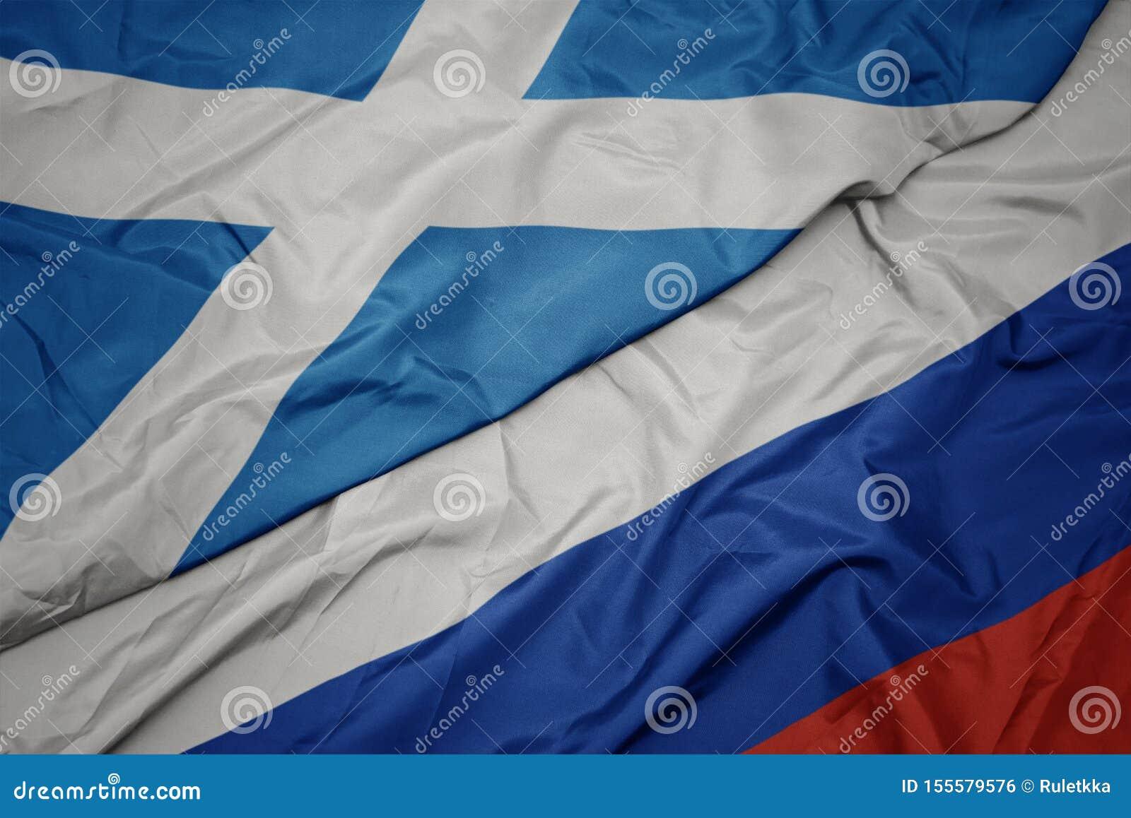 Golvende kleurrijke vlag van Rusland en nationale vlag van Schotland