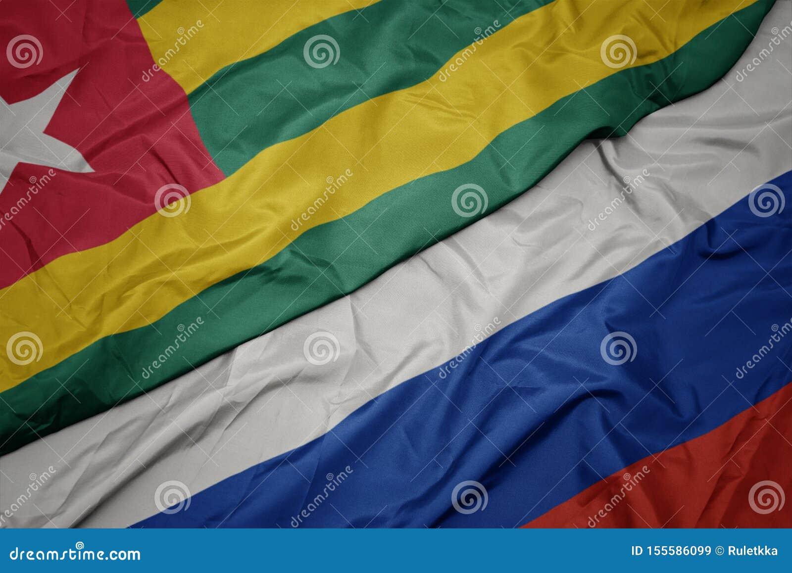 Golvende kleurrijke vlag van Rusland en nationale vlag van Togo