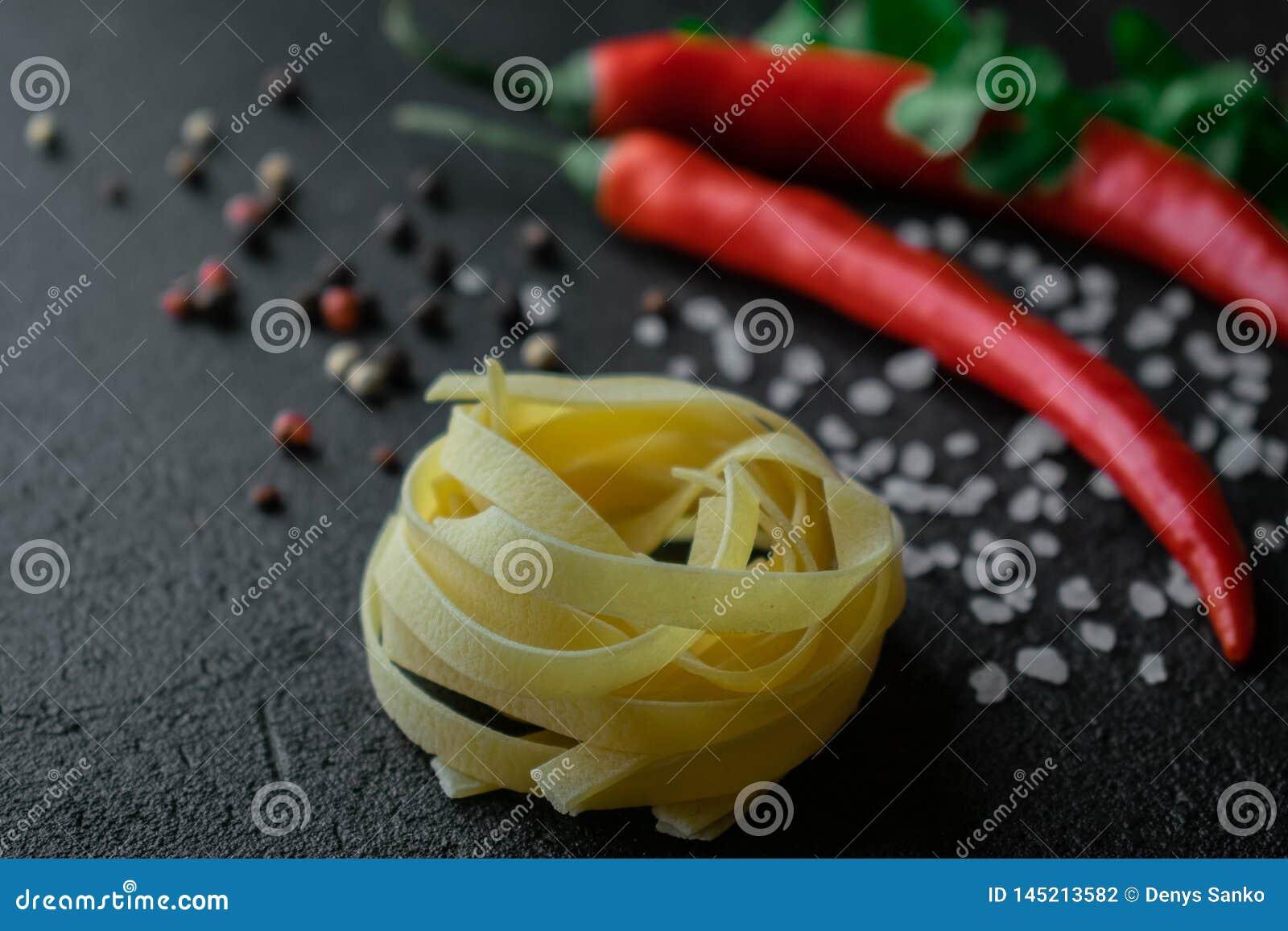 Goma cruda del fettuccine en fondo negro con la sal y los granos de pimienta frescos del mar de las ramitas del cilantro del chil